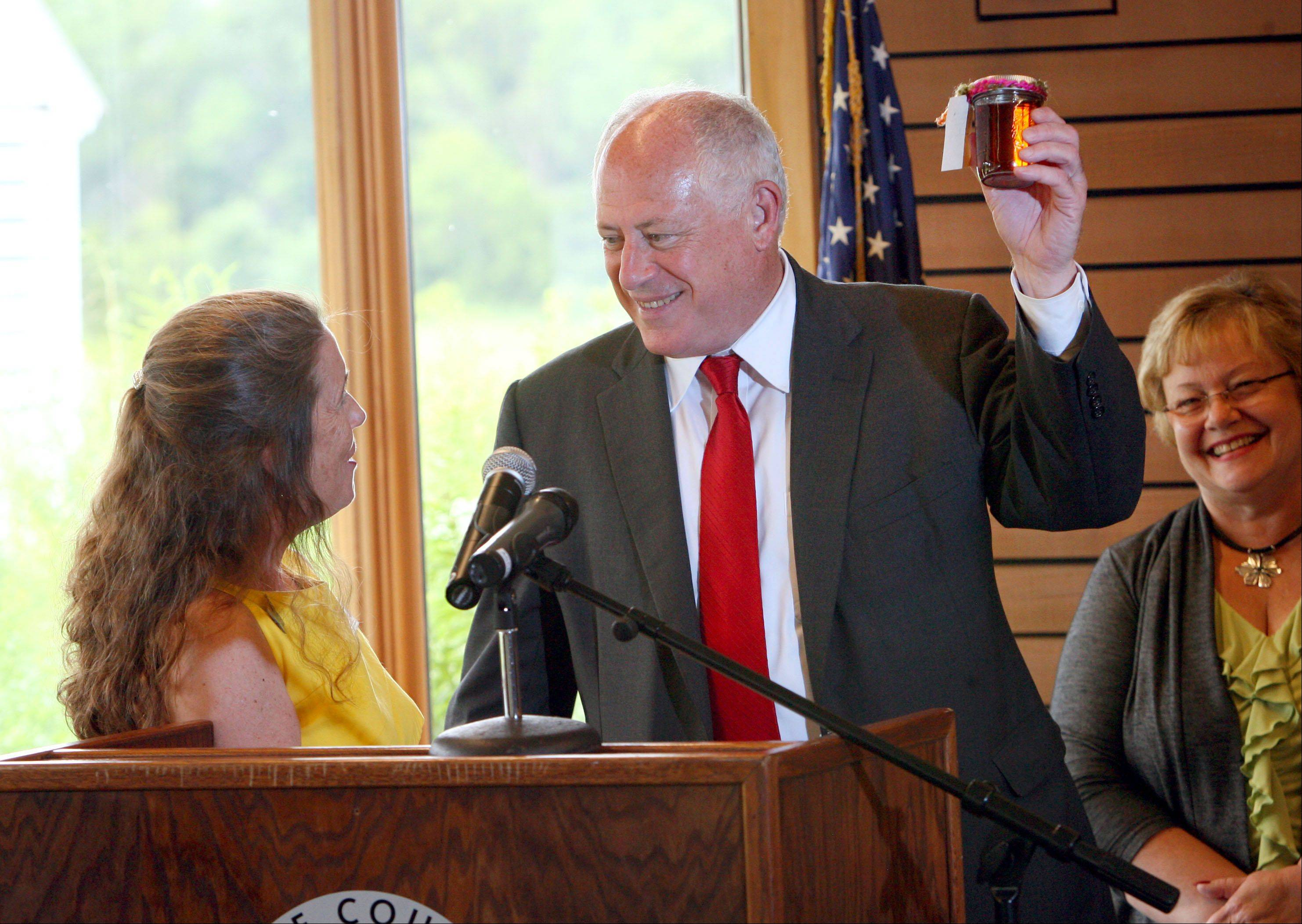 Gov. Pat Quinn, right, holds a jar of honey presented to him Thursday by Lake County Forest Preserve District President Ann Maine. Quinn was at Ryerson Woods Forest Preserve in Deerfield to sign measures involving conservation and the environment.