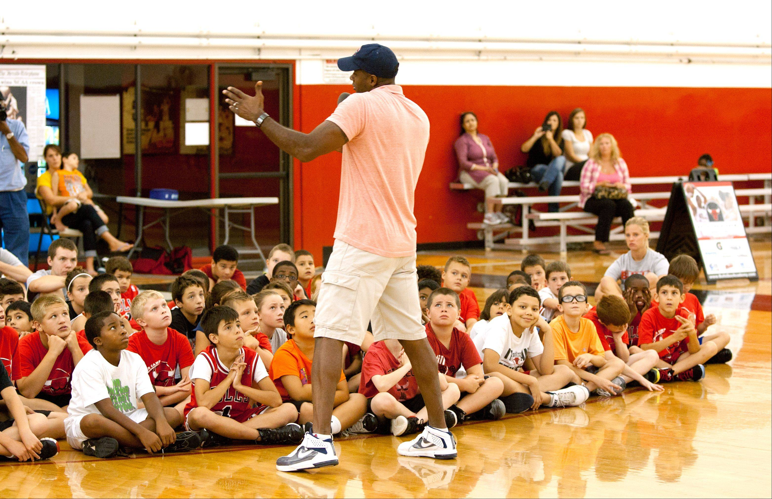 Former Bulls and Illini forward Kendall Gill stops by a youth basketball camp Thursday at the Bulls/Sox Academy in Lisle to offer advice about working hard to achieve goals in basketball and life.