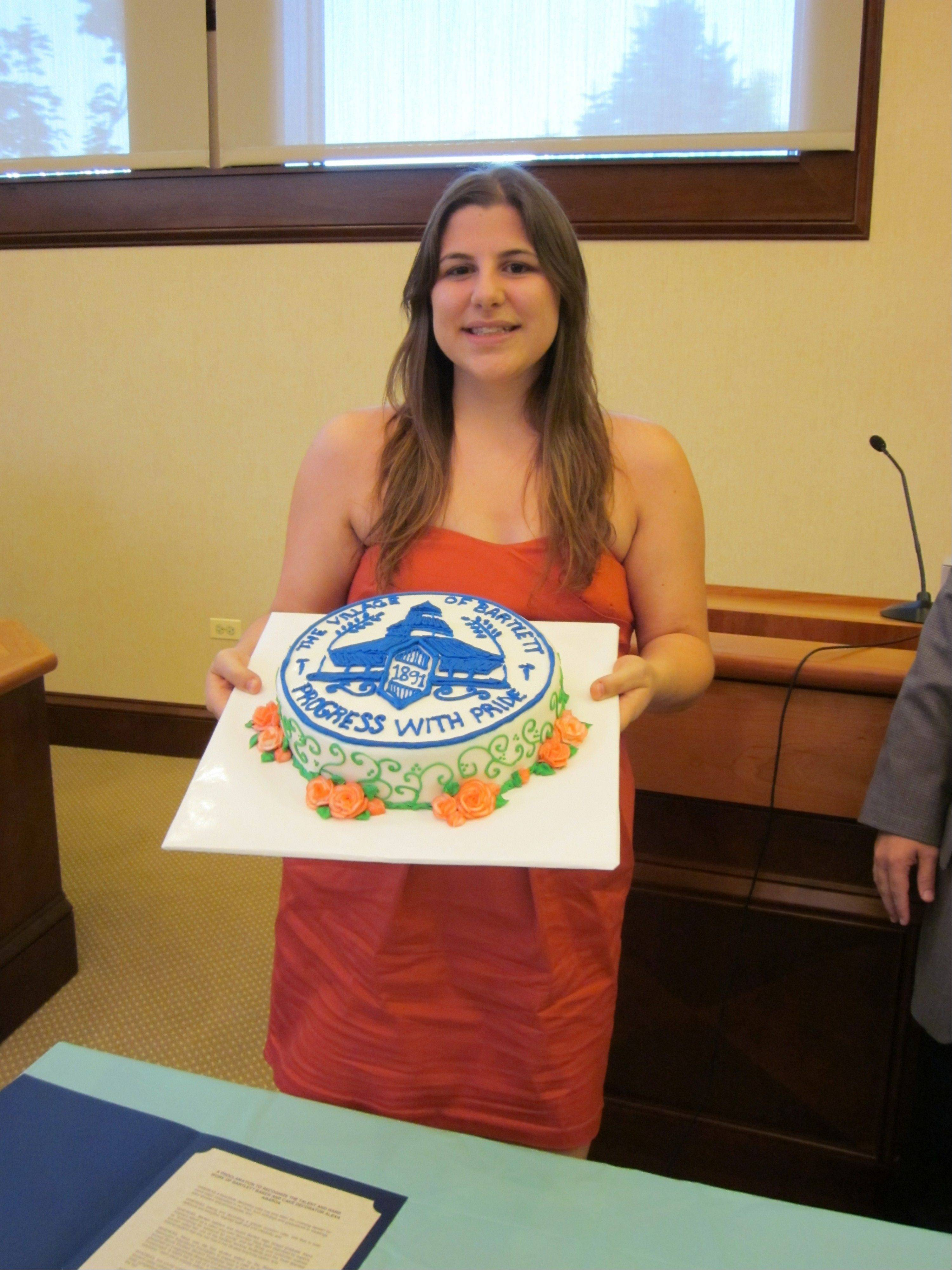 Recent Bartlett High School graduate Alexa Abaroa pictured with a cake she baked that features the Bartlett emblem. Abaroa, who won an $18,000 scholarship to attend Kendall College in the fall, was honored at a Bartlett village board meeting this month.