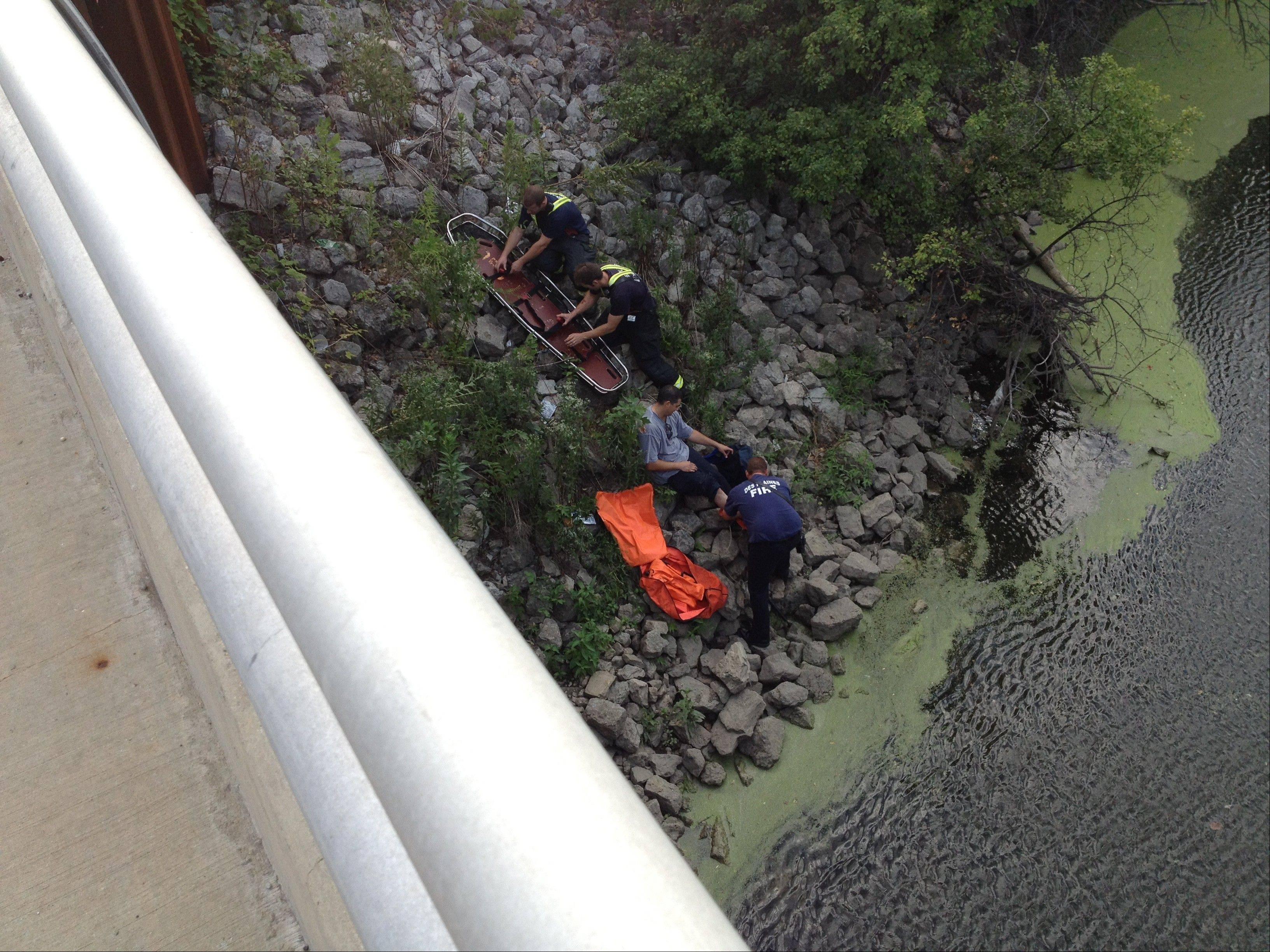 Des Plaines firefighter/paramedics Wednesday treat an injured man with a broken leg who was stuck on a bank of the Des Plaines River. The man had to be placed in a basket stretcher to lift him up onto the Golf Road bridge.