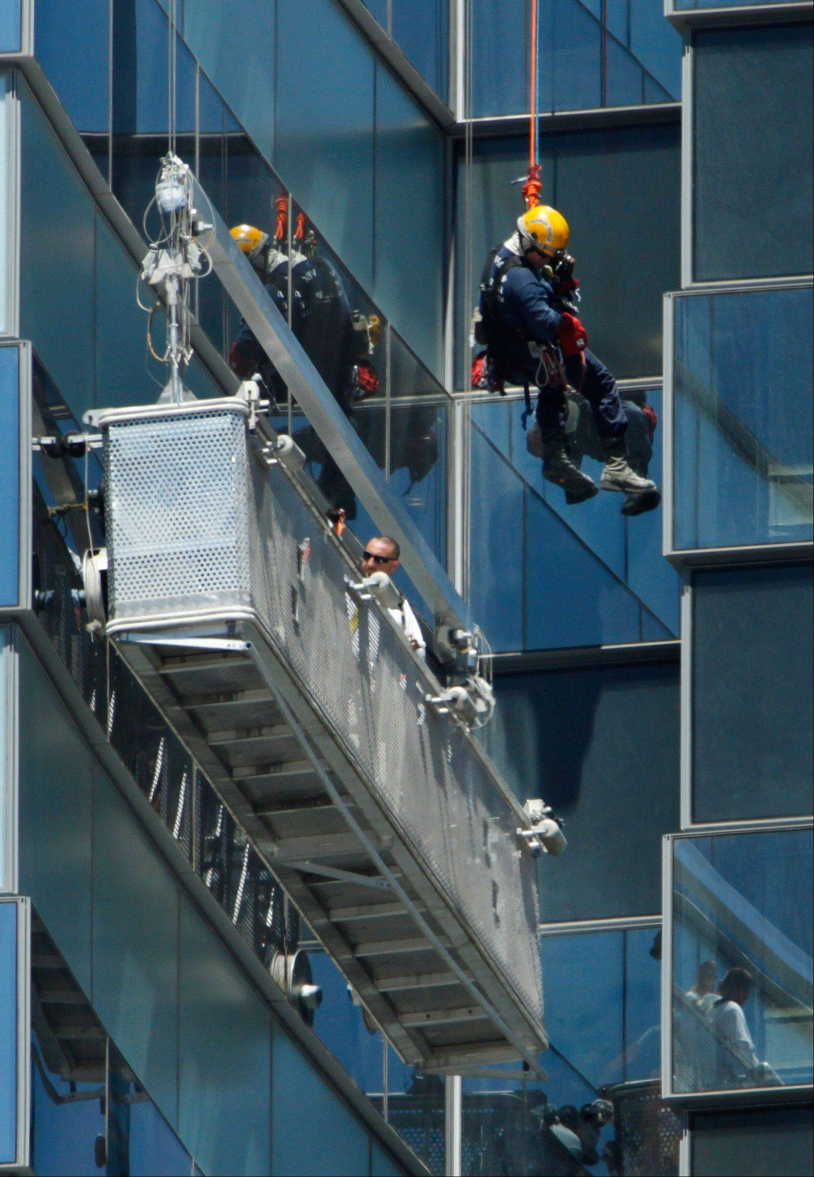 A Las Vegas Fire Department high-angle rescue worker lowers down to window washers who stranded outside the 35th floor of the Vdara Hotel at CityCenter in Las Vegas, Wednesday.