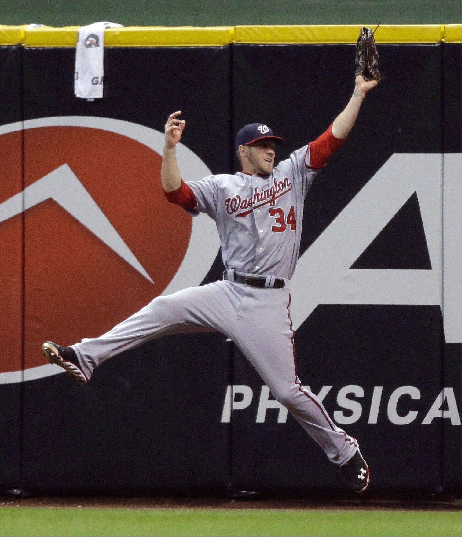 The Nationals� Bryce Harper leaps to make the catch on a ball hit by the Brewers� Corey Hart during the eighth inning Thursday in Milwaukee.