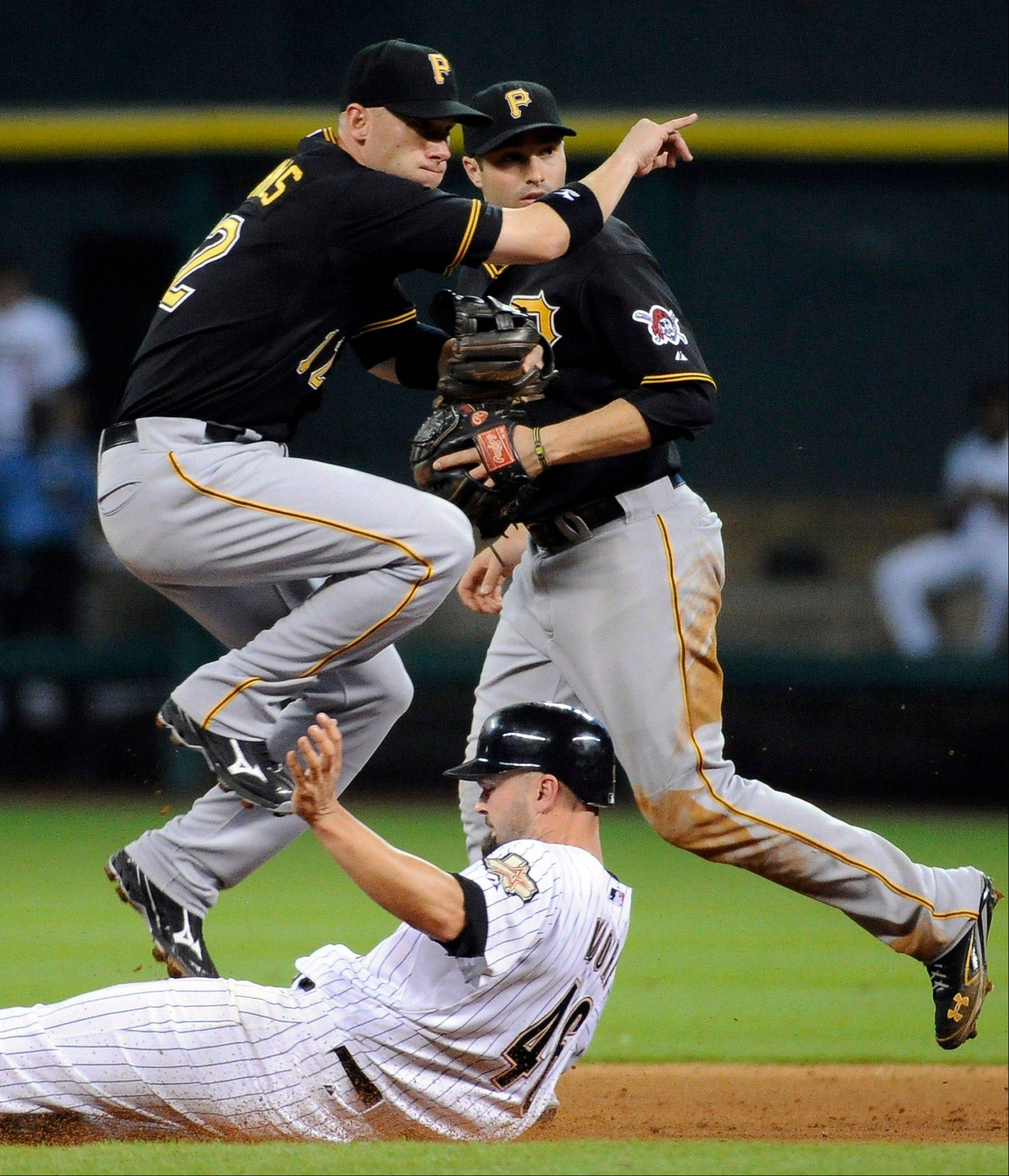 Pittsburgh�s Clint Barmes jumps over the Astros� Scott Moore to complete a double play in the seventh inning Thursday in Houston.