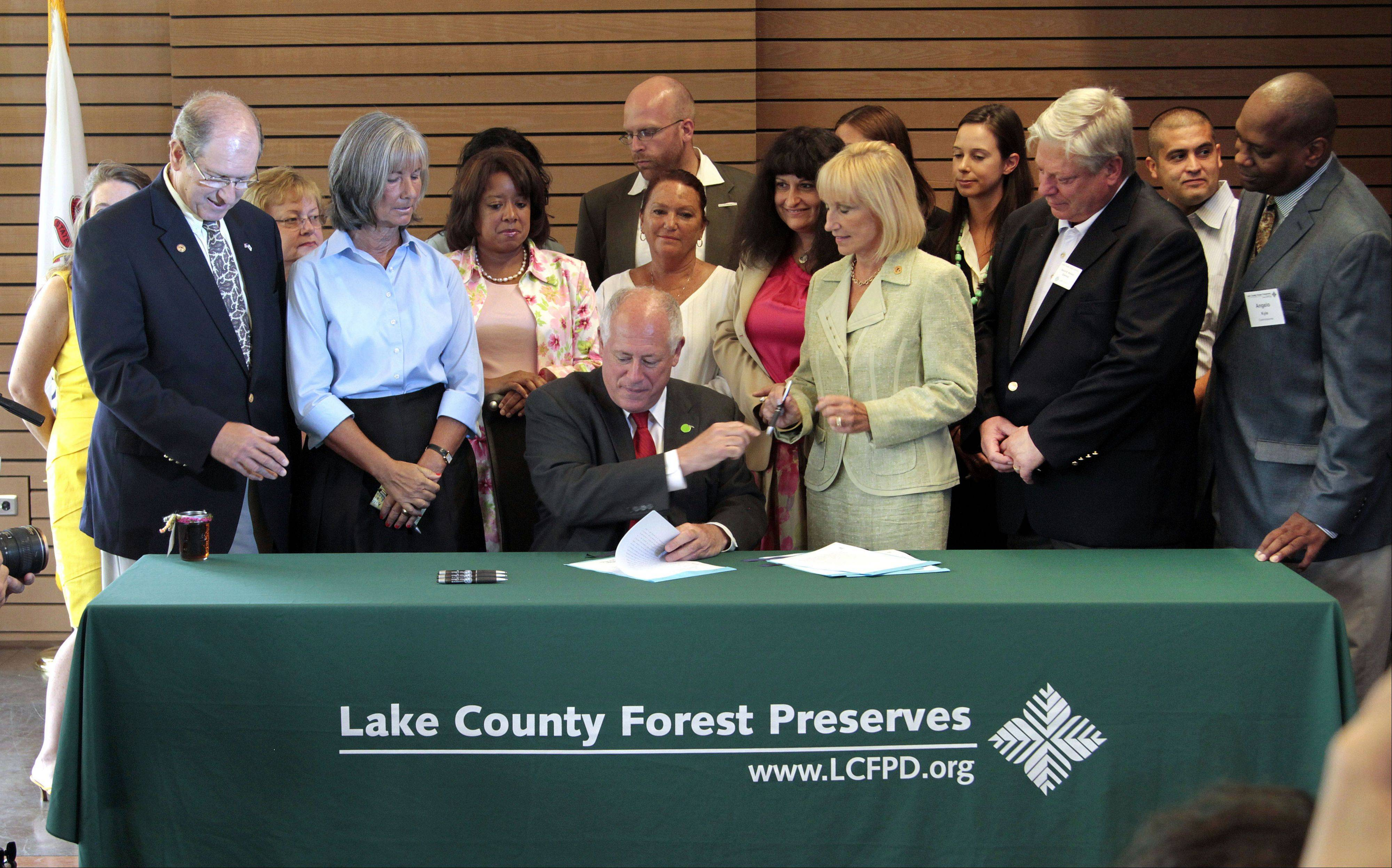 Gov. Pat Quinn signs one of several measures Thursday at the Ryerson Woods Welcome Center in Deerfield involving conservation and the environment.