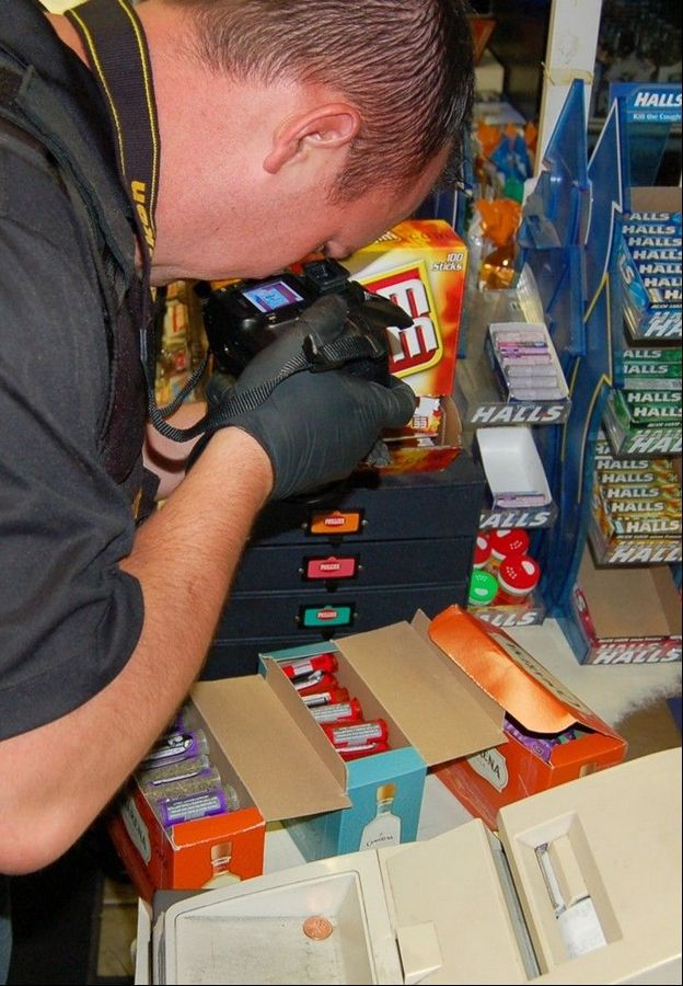 A Lake County sheriff's deputy inspects packages of synthetic cannabis at 41 News in Wadsworth on Thursday as part of a three-month investigation into the distribution of synthetic cannabis in Lake County.