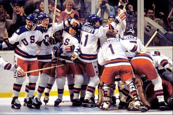 The U.S. hockey team pounces on goalie Jim Craig after a 4-3 victory against the Soviets in the 1980 Olympics, as a flag waves from the partisan Lake Placid, N.Y. crowd, February 22, 1980.