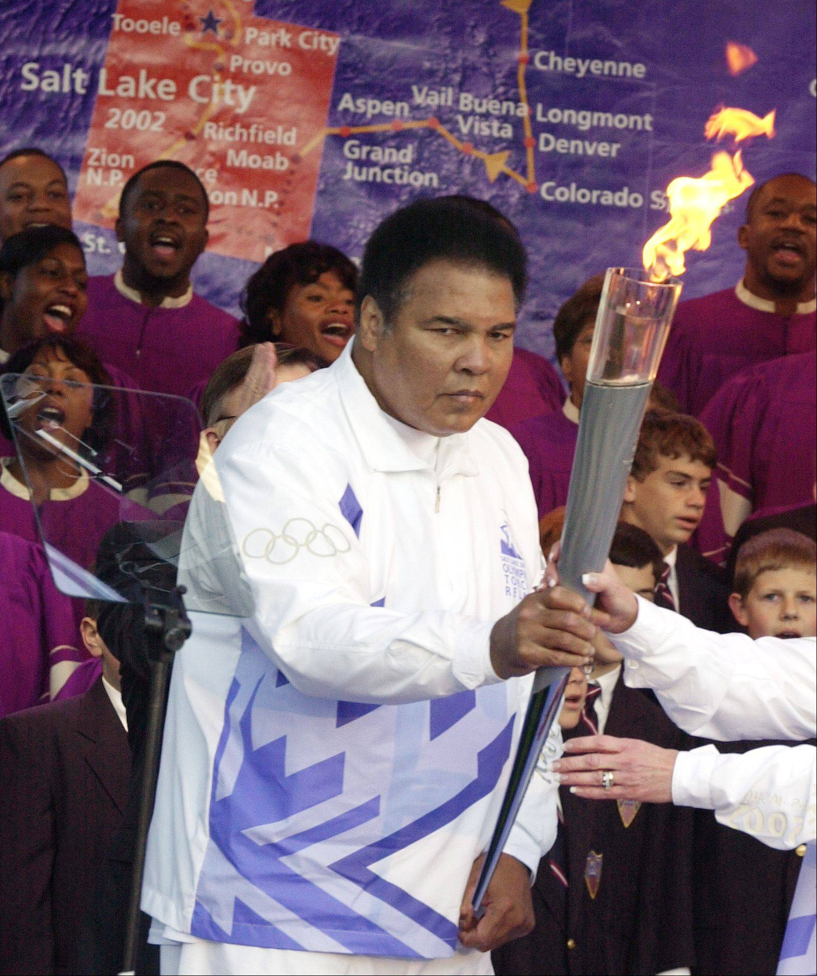 Boxing legend Muhammad Ali hands off the Olympic torch in front of a map showing the torch's travels during a ceremony at Centennial Olympic Park in Atlanta on Dec. 4, 2001.