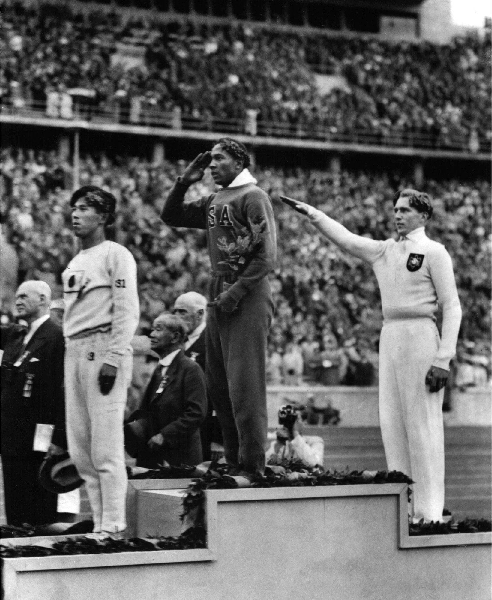 America's Jesse Owens, center, salutes during the presentation of his gold medal for the long jump on August 11, 1936, after defeating Nazi Germany's Lutz Long, right, during the 1936 Summer Olympics in Berlin. Naoto Tajima of Japan, left, placed third. Owens triumphed in the track and field competition by winning four gold medals in the 100-meter and 200-meter dashes, long jump and 400-meter relay. He was the first athlete to win four gold medals at a single Olympic Games.