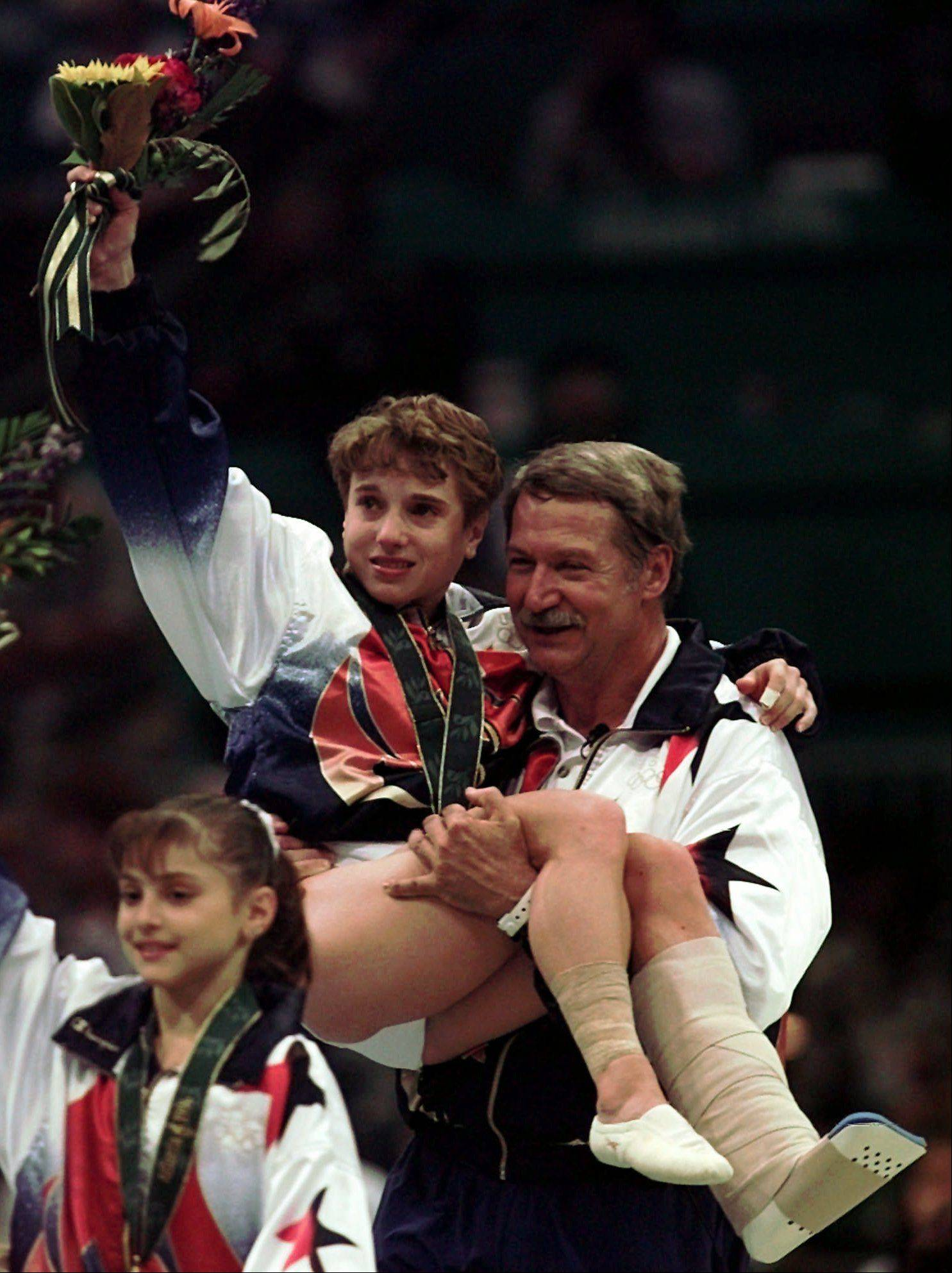 U.S. gymnastics coach Bela Karolyi carries injured Kerri Strug following the awarding ceremony at the women's team gymnastics competition at the Centennial Summer Olympic Games in Atlanta on Tuesday, July 23, 1996. Strug injured her left leg during the vault routine. The U.S. won the gold. At left is Dominique Moceanu.