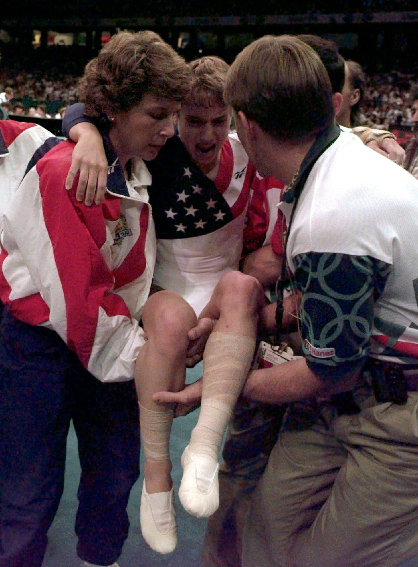 Kerri Strug, of Houston, Texas, grimaces in pain as she is helped after injuring her left leg following her landing in the vault competition at the women's team gymnastics finals at the Centennial Summer Olympic Games in Atlanta on Tuesday, July 23, 1996.