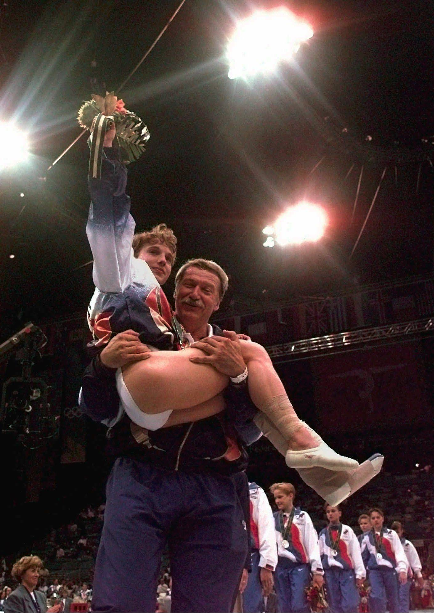 Kerri Strug of the United States waves to crowd as she is carried by her coach Bela Karolyi during the awards ceremony in the women's team gymnastics competition at the Centennial Summer Olympic Games in Atlanta on Tuesday, July 23, 1996. Strug injured her left leg during her landing in the vault. Despite the injury the US team won the gold.