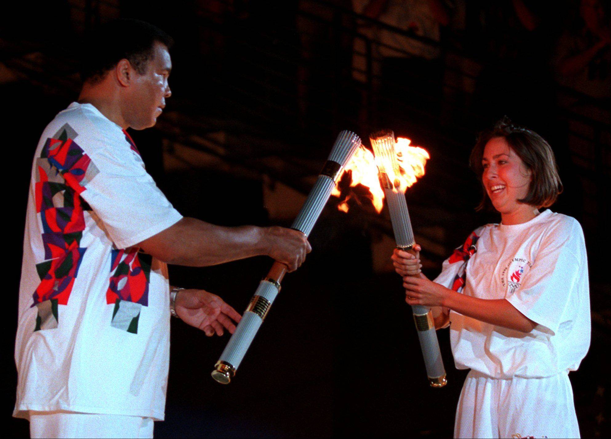 American swimmer Janet Evans passes the Olympic flame to Muhammad Ali during the 1996 Summer Olympic Games Opening Ceremony in Atlanta Friday, July 19, 1996.