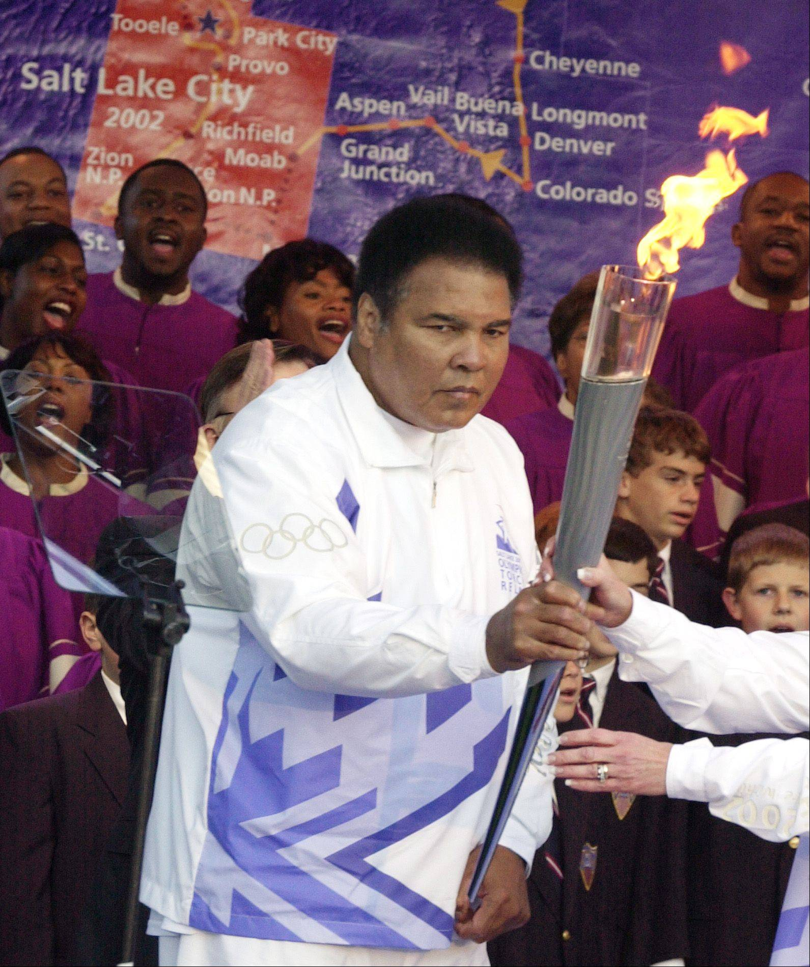 Boxing legend Muhammad Ali holds the Olympic torch in front of a map showing the torch's route to runner Peggy Fleming, 1968 figure skating gold medalist, during a ceremony at Centennial Olympic Park in Atlanta Tuesday, Dec. 4, 2001. The Olympic torch returned to the United States for the first time since the 1996 Games in Atlanta and was passed from one gold medalist to another before beginning a 46-state tour to the 2002 Winter Olympics in Salt Lake City.