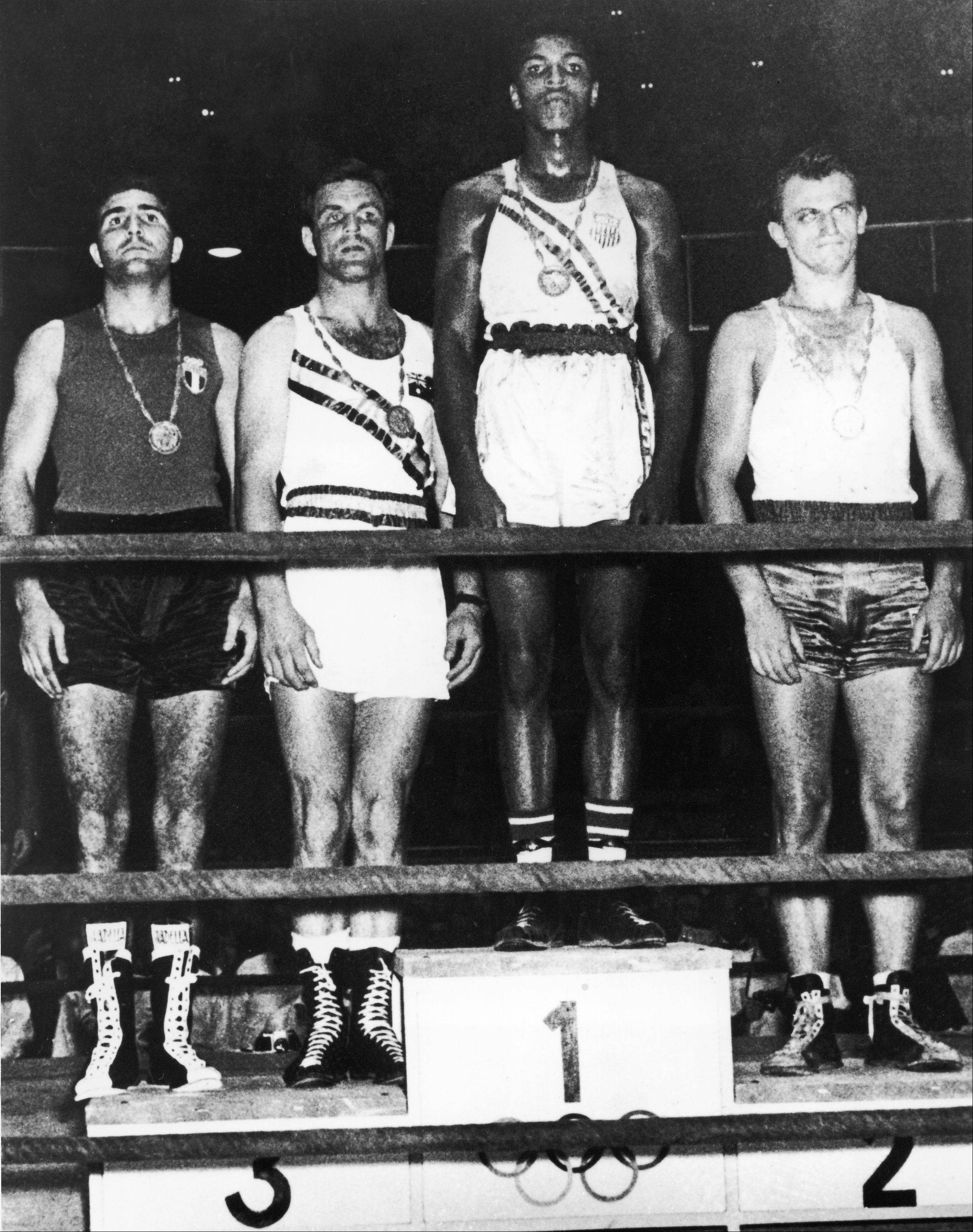 The winners of the light heavyweight boxing division pose during the medal ceremony at the Summer Olympic Games in Rome, Italy, Sept. 14, 1960. Gold medal winner is then 18 year-old Cassius Clay, and silver medal winner is Z Pietrzykowski of Poland, right; and the bronze medal winners are Tony Madigan of Australia and Giulio Saraudi of Italy, far left.