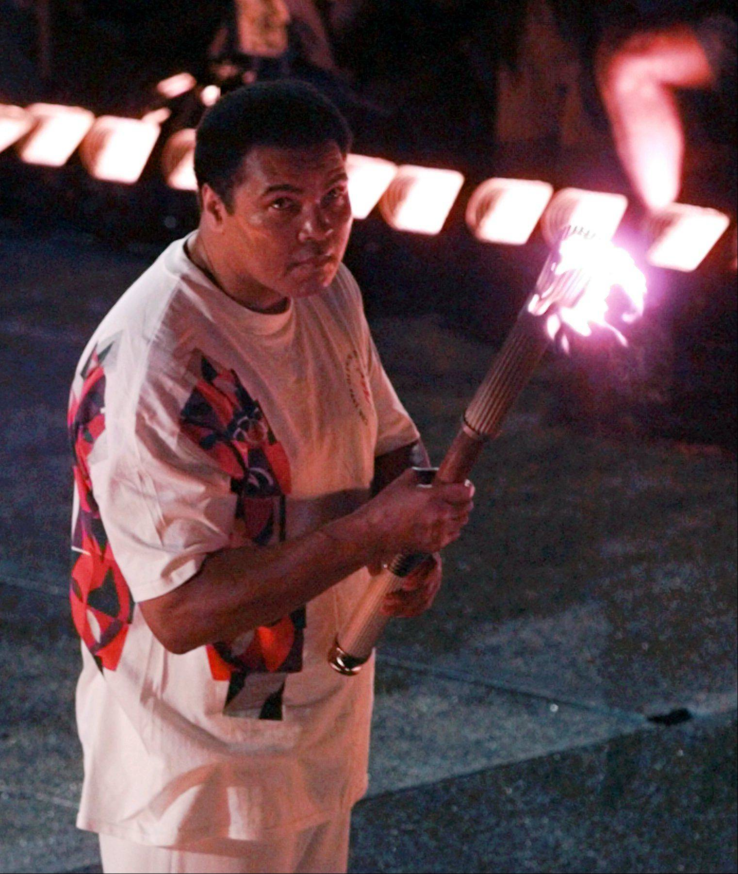 Muhammad Ali watches as the flame climbs up to the Olympic torch during the opening ceremonies of the Summer Olympics Friday, July 19, 1996, in Atlanta.