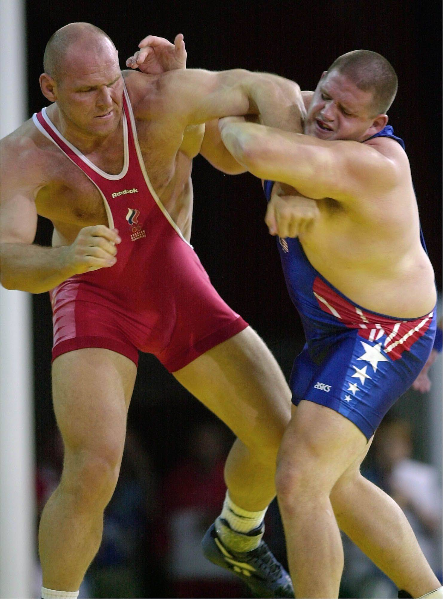 Rulon Gardner, right, of the United States holds the arm of Alexander Karelin of Russia during the final bout action on his way to winning the gold medal in the 130 kg class of Greco-Roman wrestling event in the Summer Olympic Games in Sydney Wednesday, Sept. 27, 2000.