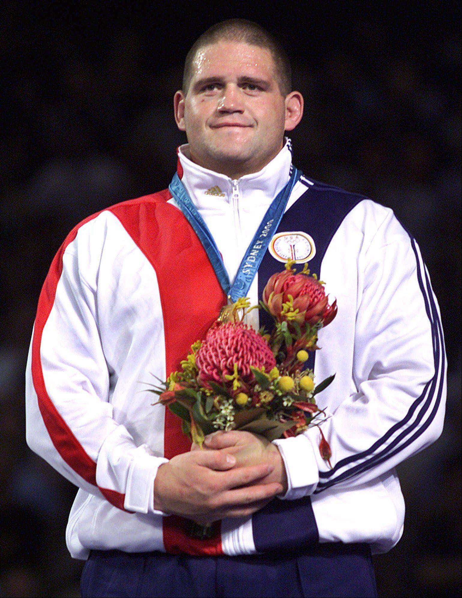 "USA's Rulon Gardner smiles from the top of the medal stand after defeating Russia's Alexandre Kareline in the 130 kg Greco-Roman wrestling final at the Sydney Olympic Games, Wednesday, Sept. 27, 2000. Gardner, is the talk of his hometown and state of Afton, Wyo. ""It's a great big deal because we're such a small community,"" said Gloria Putnam, owner of Country Charm Beauty Salon. The unheralded Gardner won against Karelin, unbeaten in 13 years and a three-time defending gold medalist."