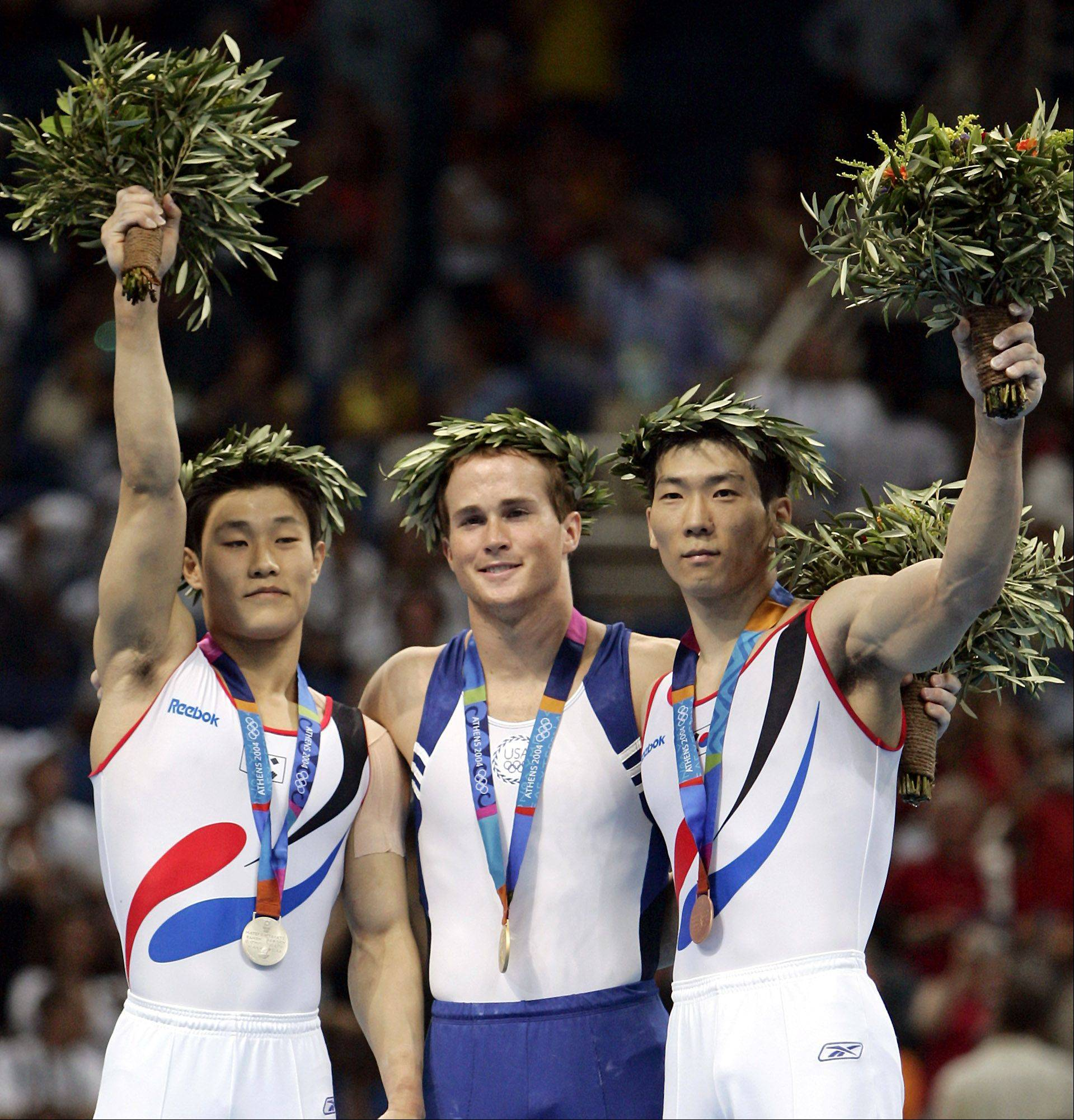 Gold medal winner Paul Hamm, of the United States, center, silver medal winner Kim Dae Eun, left, and bronze medal winner Yang Tae Young, of Korea, celebrate together during the medal ceremony for the men's gymnastics individual all-around final at the 2004 Olympic Games in Athens, Wednesday, Aug. 18, 2004. The International Gymnastics Federation ruled Saturday Aug. 21, 2004 that Yang Tae-young was unfairly docked a tenth of a point in the all-around final, costing him the gold medal that ended up going to Hamm. The South Korean got the bronze instead.