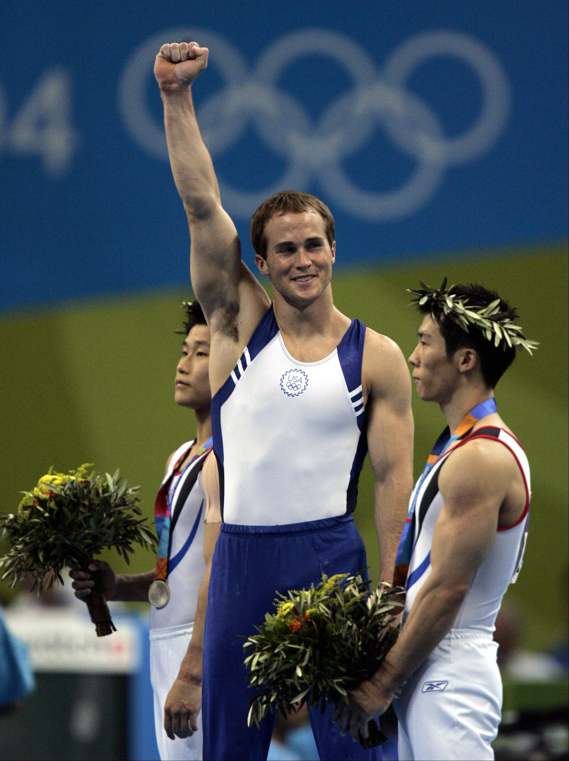 Paul Hamm of the United States, center, celebrates after winning the gold medal during the men's gymnastics individual all-around final at the 2004 Summer Olympic Games in Athens, Wednesday, Aug. 18, 2004.