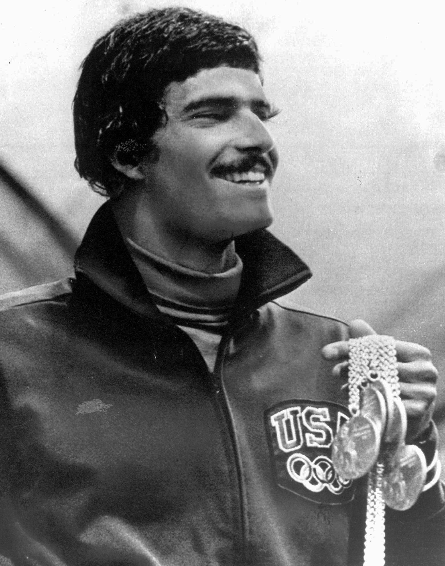 In this Aug. 31, 1972, file photo, American swimmer Mark Spitz holds five of the seven gold medals he won at the Olympics in Munich, Germany. In winning the 200-meter freestyle, Michael Phelps etched his name alongside the winningest Olympians with the ninth gold of an already brilliant career that shows no signs of slowing down.