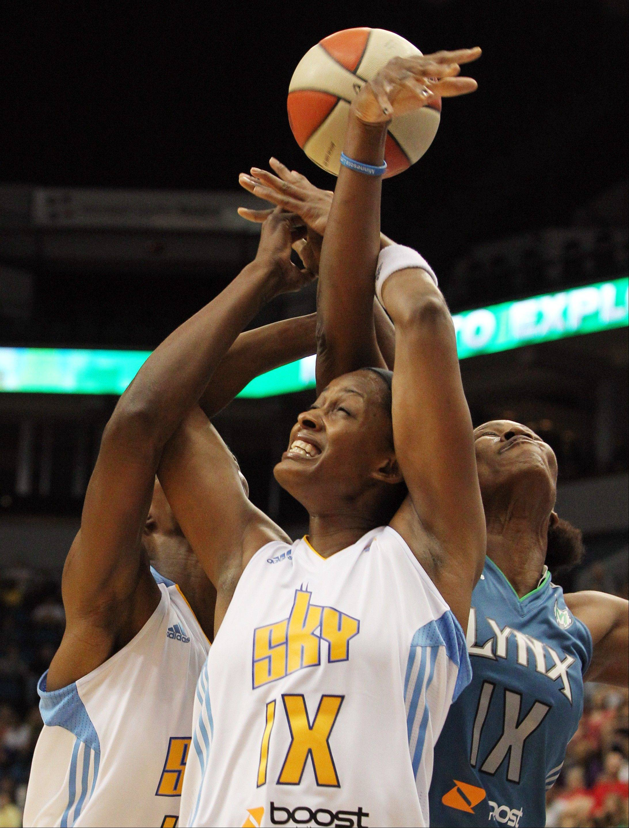 Chicago Sky's Swin Cash, center, and Sylvia Fowles, left, battle for a rebound against Minnesota Lynx's Taj McWilliams-Franklin during the first half of a WNBA basketball game, Saturday June 23, 2012, in Minneapolis.
