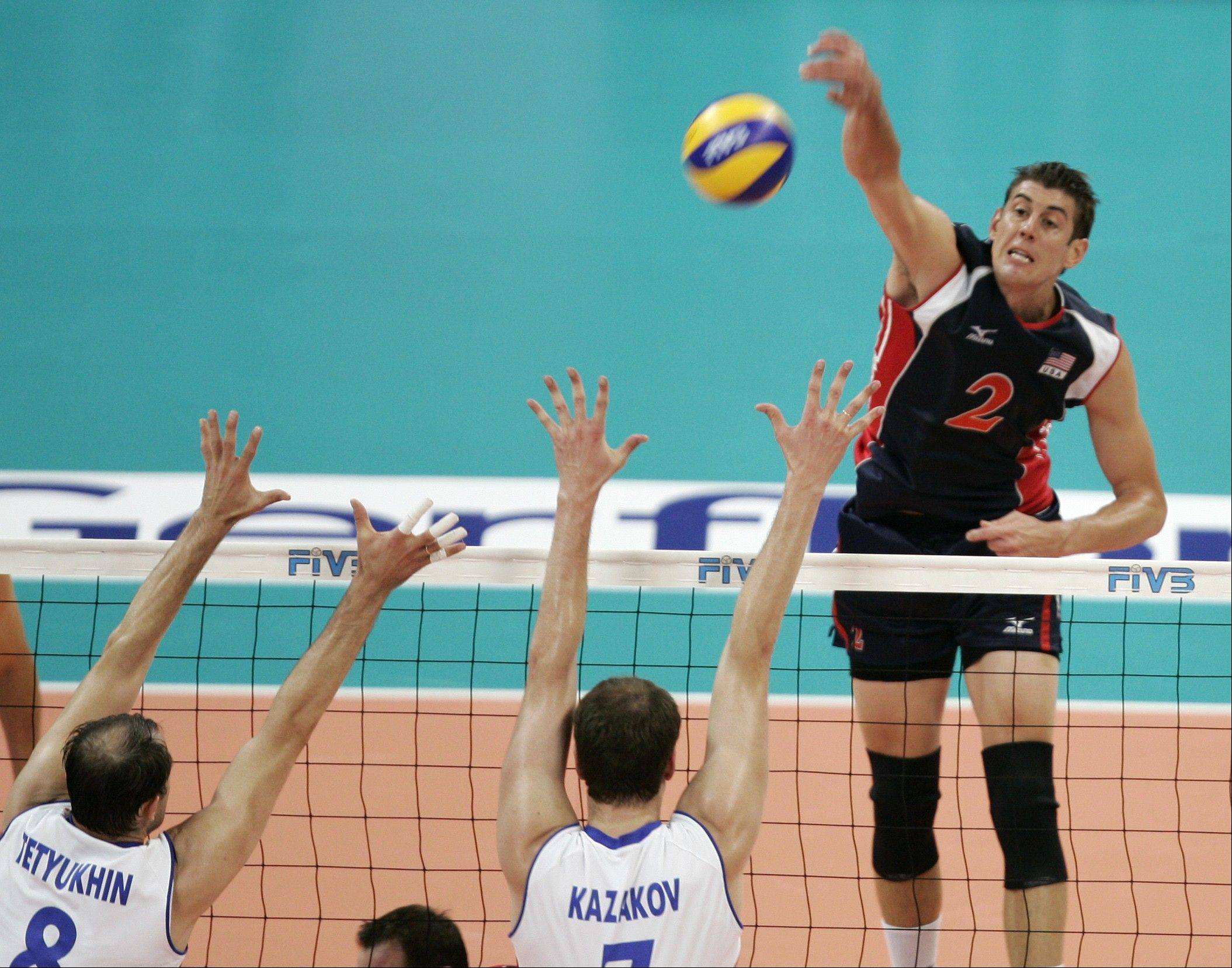 Sean Rooney of Team USA spikes the ball by Russia's Sergey Tetyukhin, left, and Alexey Kazakov during the final round of the 2009 FIVB World League Volleyball match in Belgrade, Serbia.