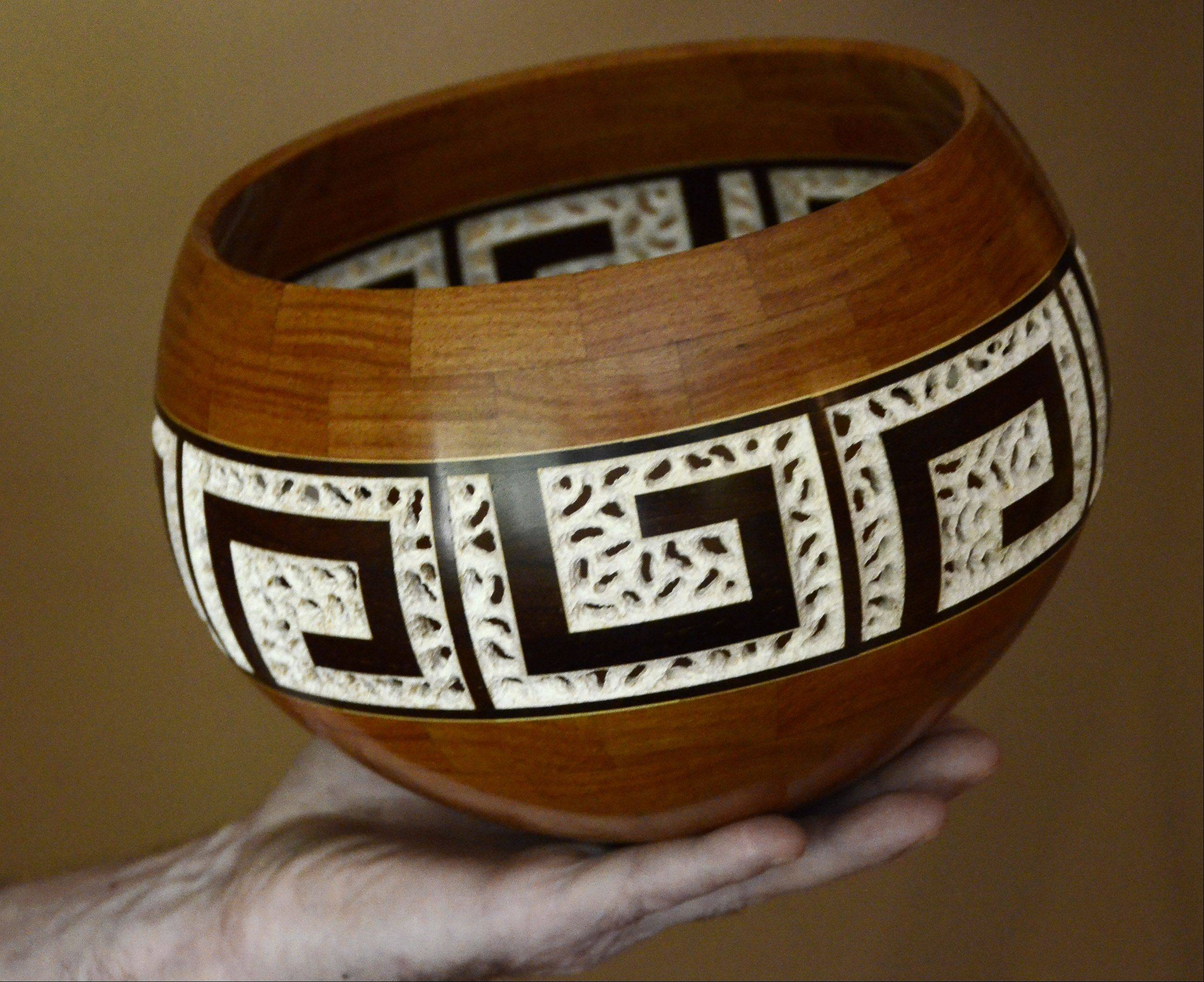 Despite his meticulous skill using a dental drill to carve the bleached maple in this segmented bowl made with three varieties of wood, Al Miotke of Mount Prospect says he considers himself more of a craftsman than an artist.