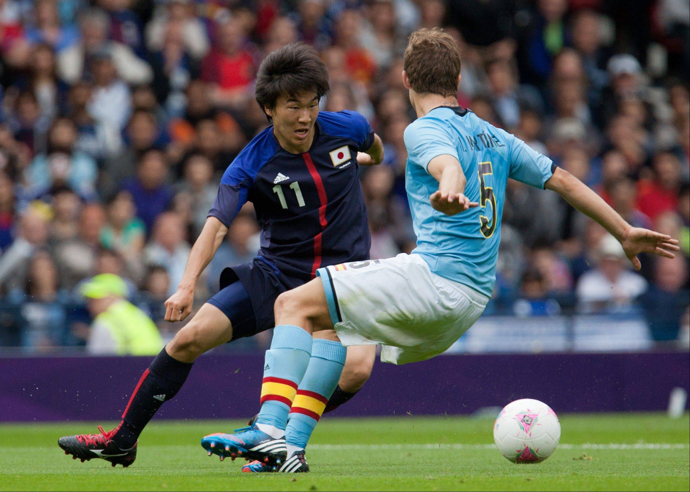 Japan's Kensuke Nagai, left, battles for the ball with Spain's Inigo Martinez, right during the group D men's soccer match between Japan and Spain at the London 2012 Summer Olympics, Thursday, July 26, 2012, at Hampden Park Stadium in Glasgow, Scotland. Japan won 1-0.