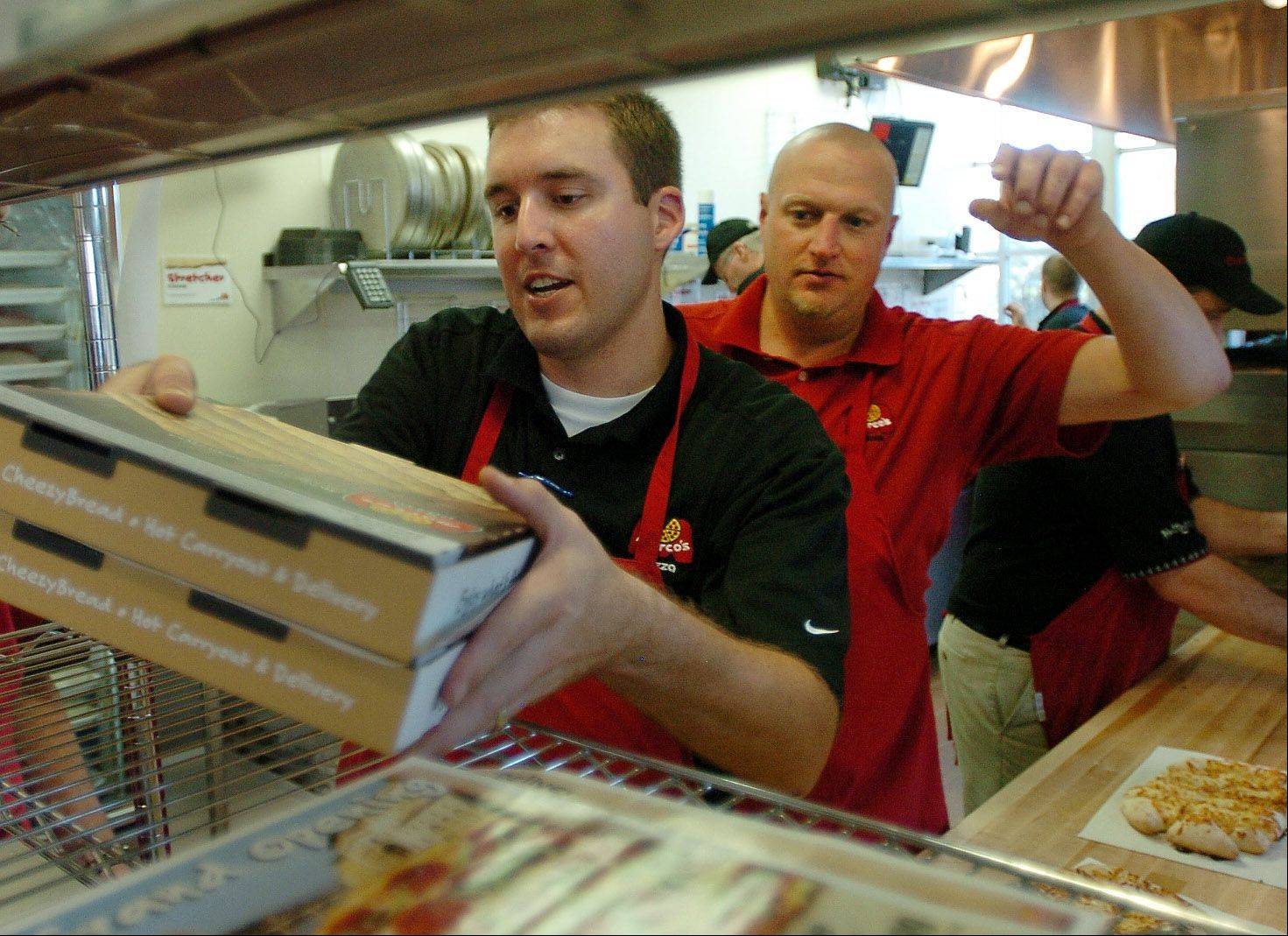 Marco's district manager Chris Hayes, left, fills an order with corporate trainer Bob Falk, right, on the first day of business at Marco's Pizza in Wheeling.