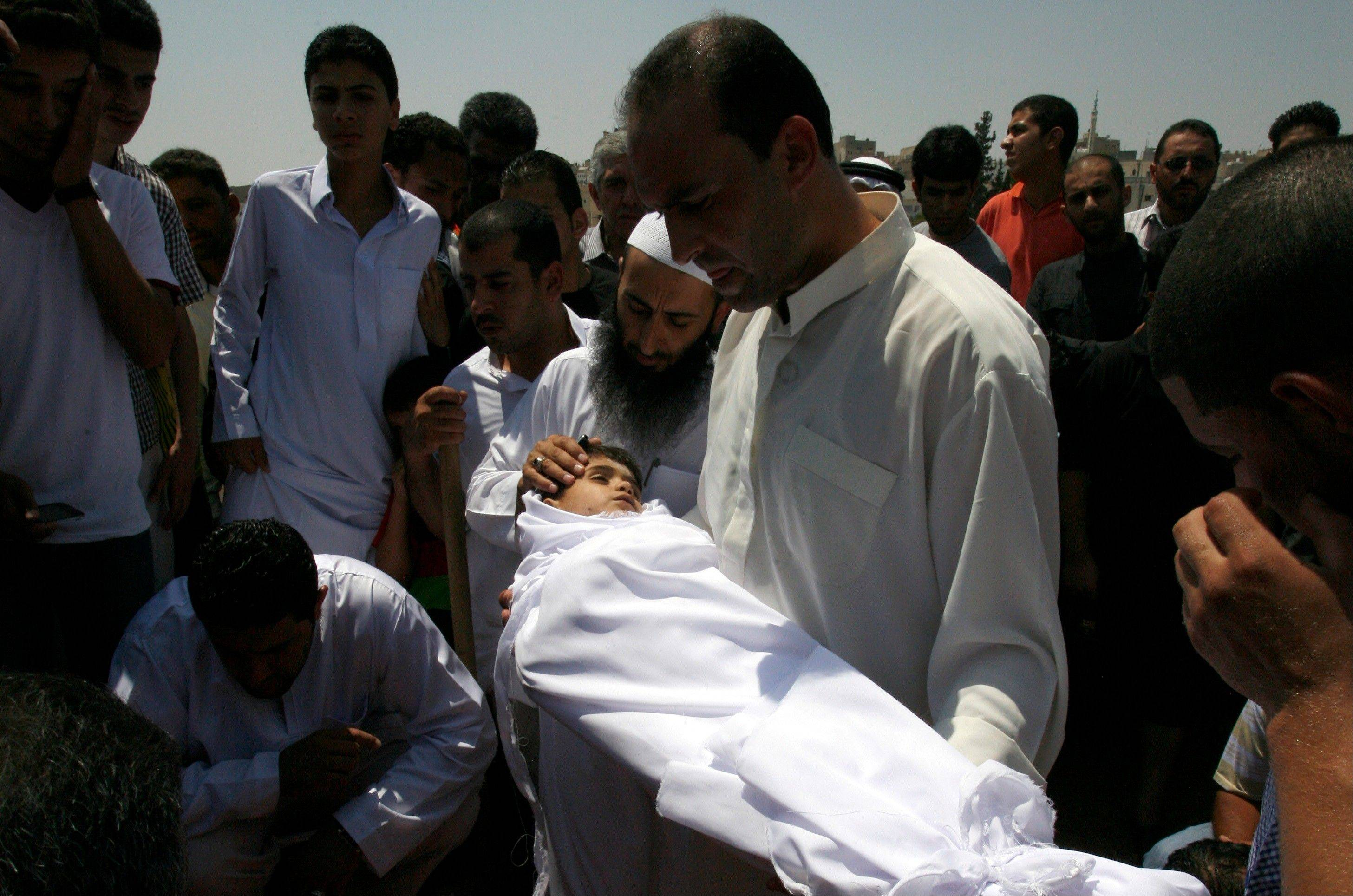 Associated Press A relative holds the body of a six year old Syrian boy Bilal El-Lababidi during his funeral Friday in Ramtha, Jordan.