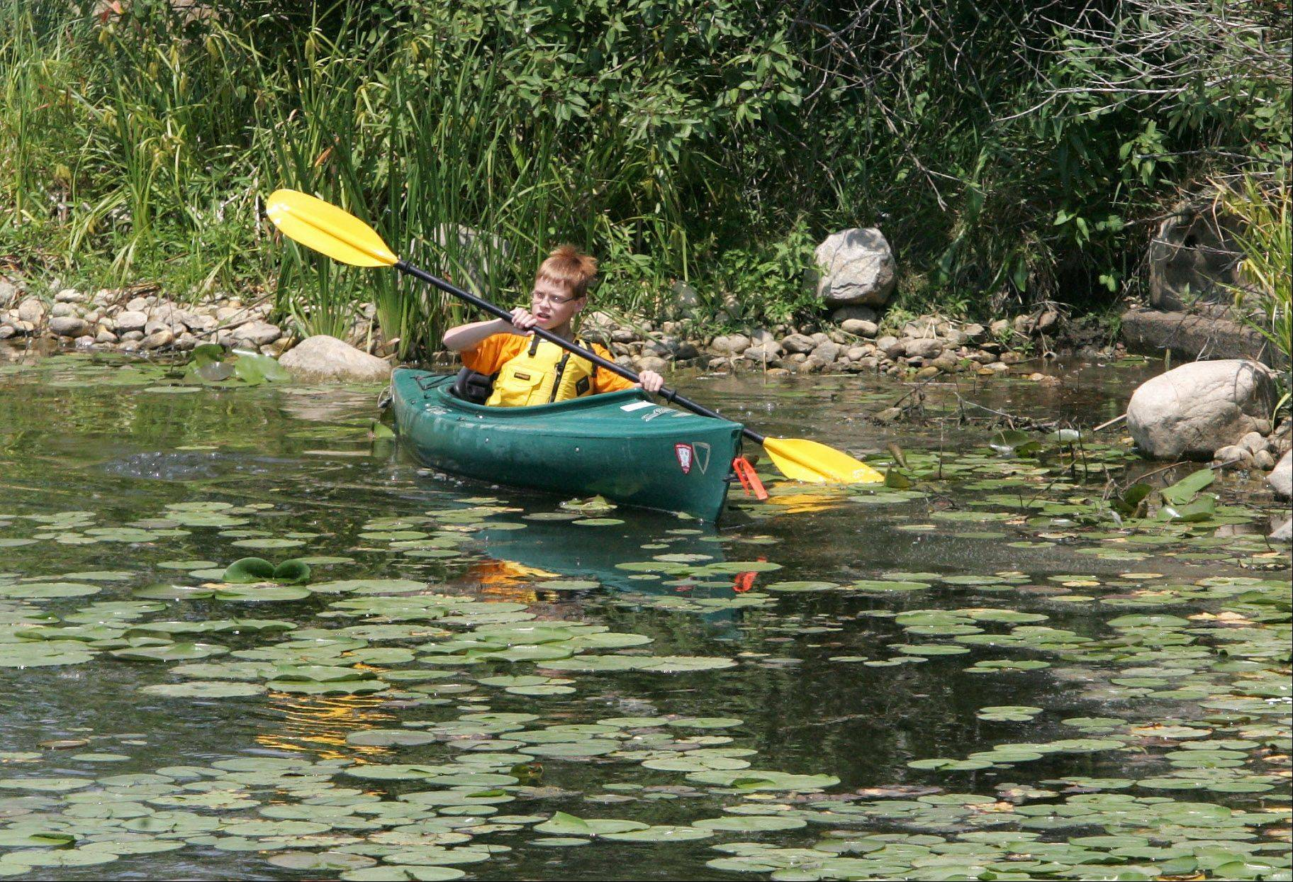 Zach Huseen, 13, of Wauconda paddles through the water lilies as members of the Adventures in Nature Camp kayak on a lake at Independence Grove Forest Preserve in Libertyville. The weeklong summer camp, run by the Lake County Forest Preserve District, included an obstacle course, biking, swimming and hiking.