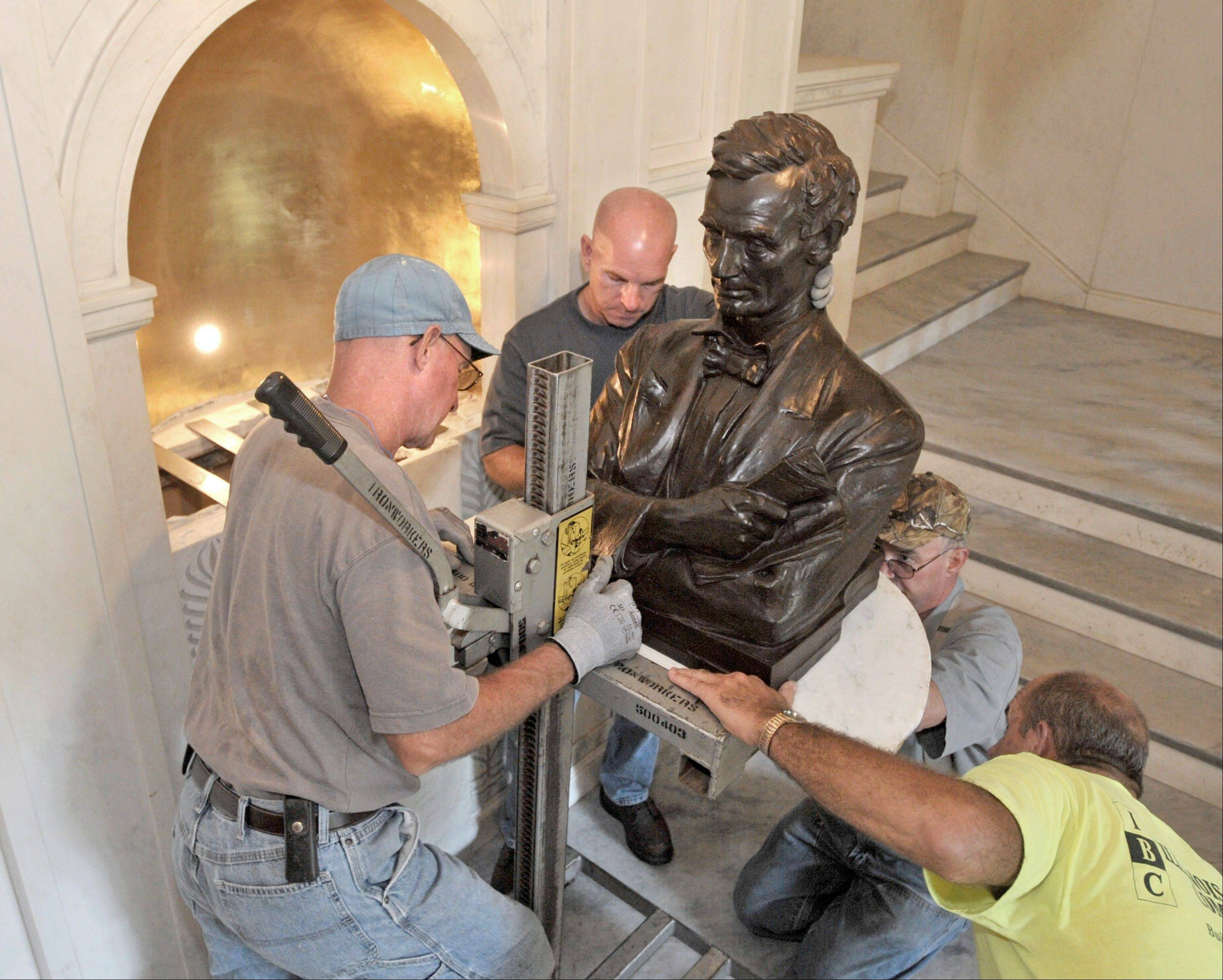 From left, University of Illinois iron workers Ron Cler, Todd Hawkins, Gary Fry, and brick mason Bill Mastny place the bronze bust of Abraham Lincoln into it's alcove in after it was restored, the main entrance to Lincoln Hall on the University of Illinois campus, in Urbana.