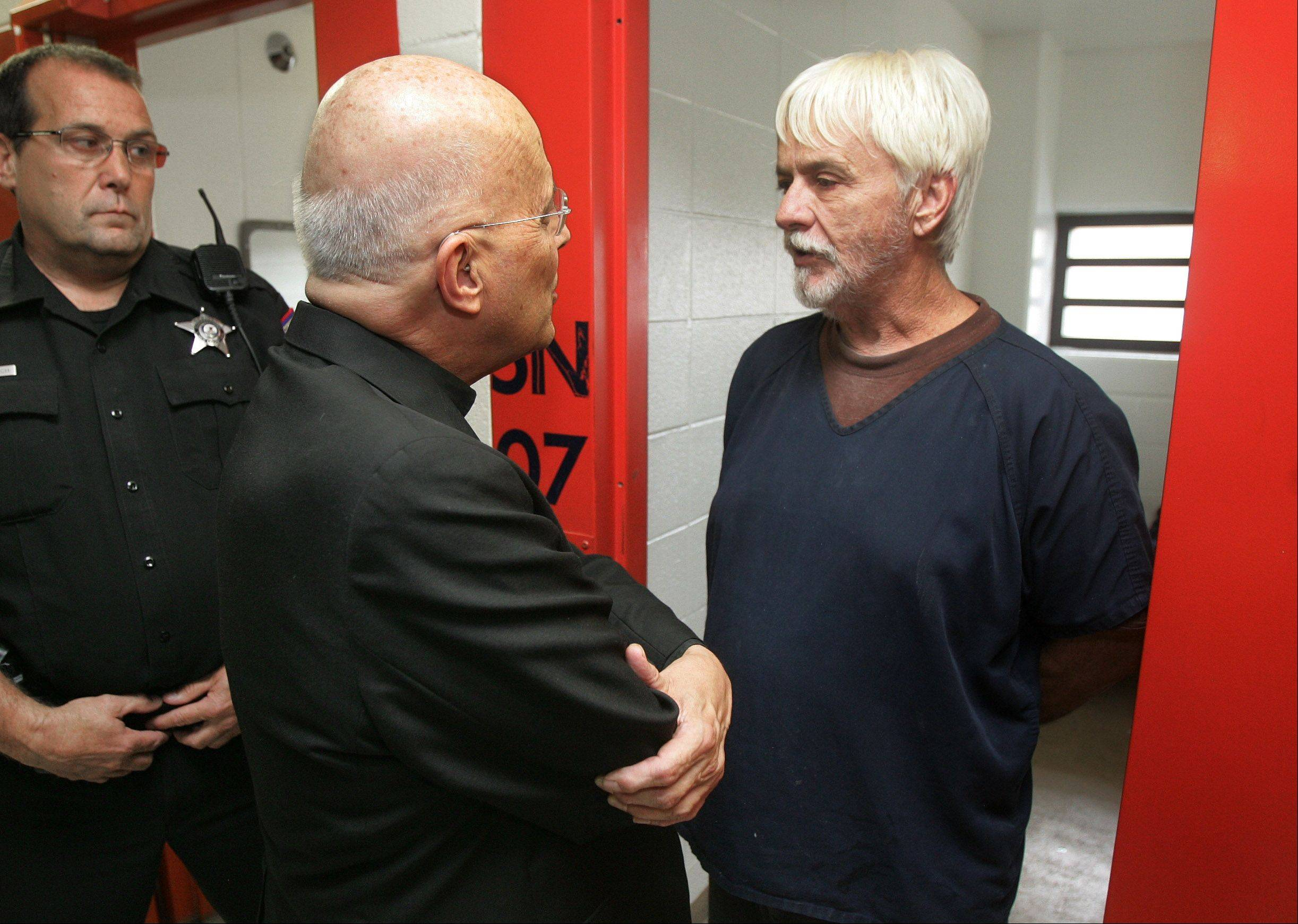 Cardinal Francis George talks to inmate Roy Robert Bridges as he visits the Lake County jail in Waukegan on Thursday.