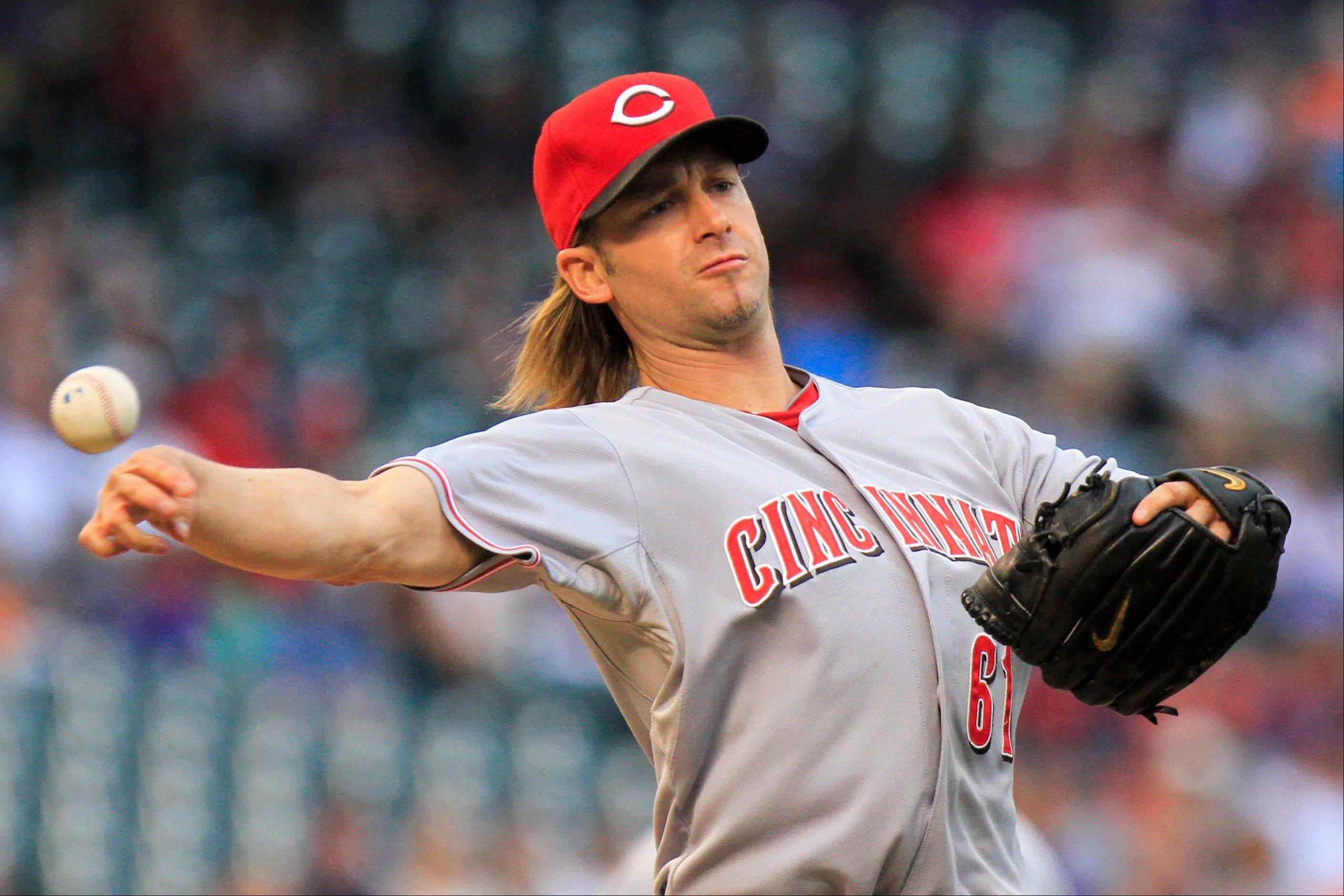 Reds starting pitcher Bronson Arroyo throws out the Rockies' Dexter Fowler at first Friday night in Denver.