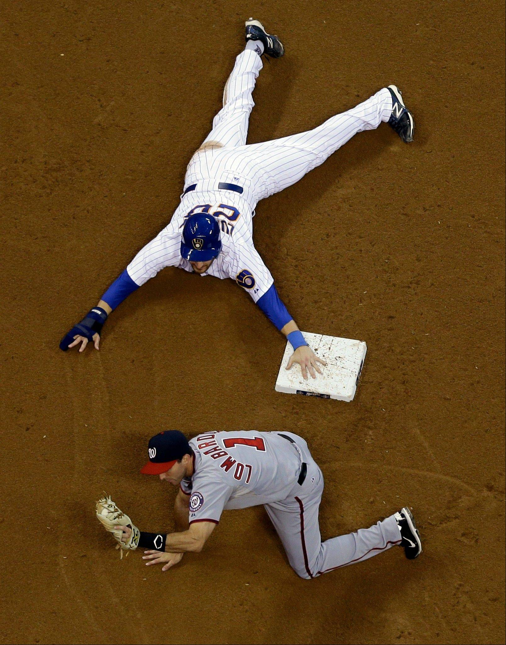 The Brewers' Jonathan Lucroy, top, was tagged out trying to steal second base by the Nationals' Steve Lombardozzi during the fourth inning Friday in Milwaukee.