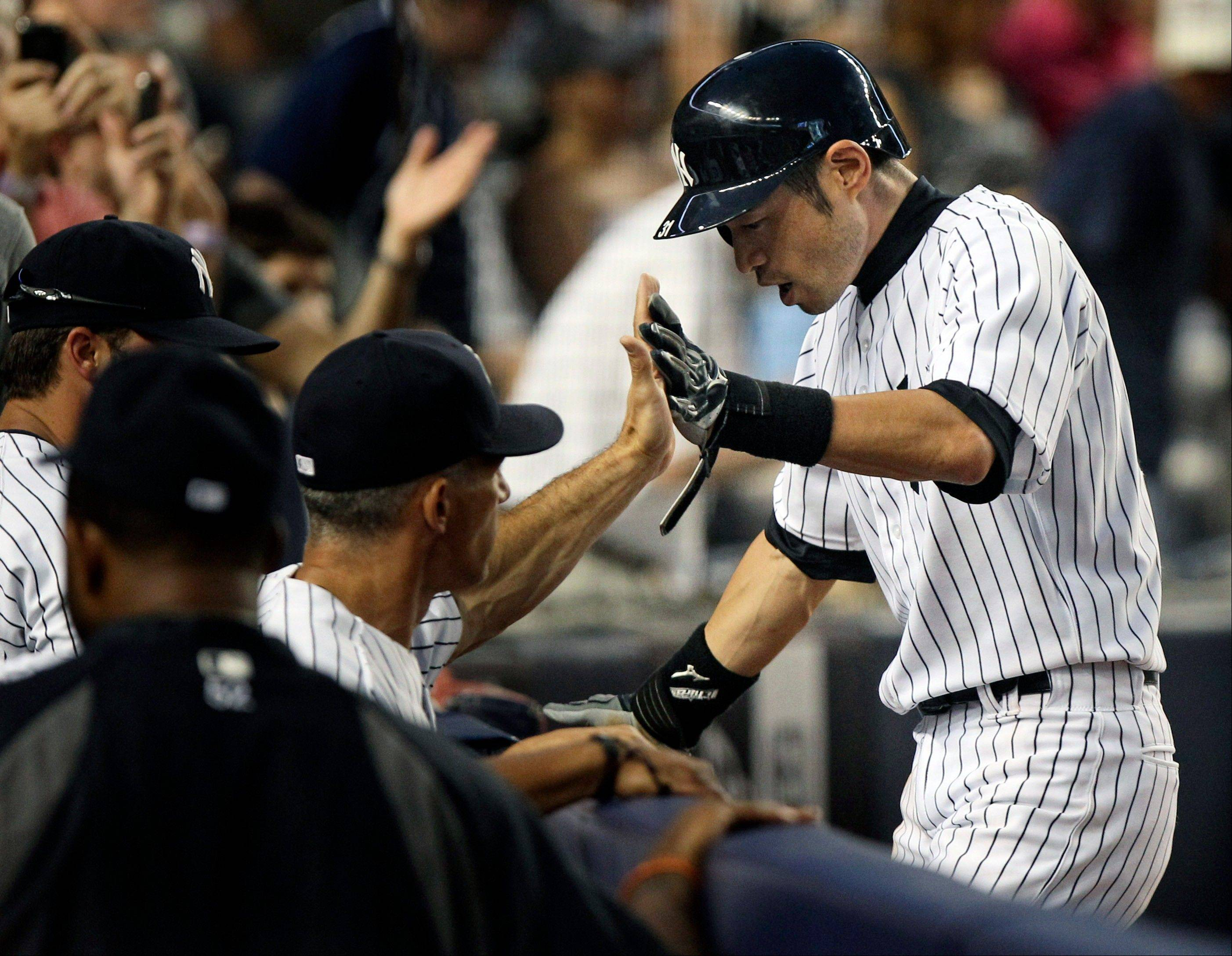 The Yankees' Ichiro Suzuki, right, celebrates after scoring on a home run hit by Russell Martin during the fourth inning Friday at home against Boston.