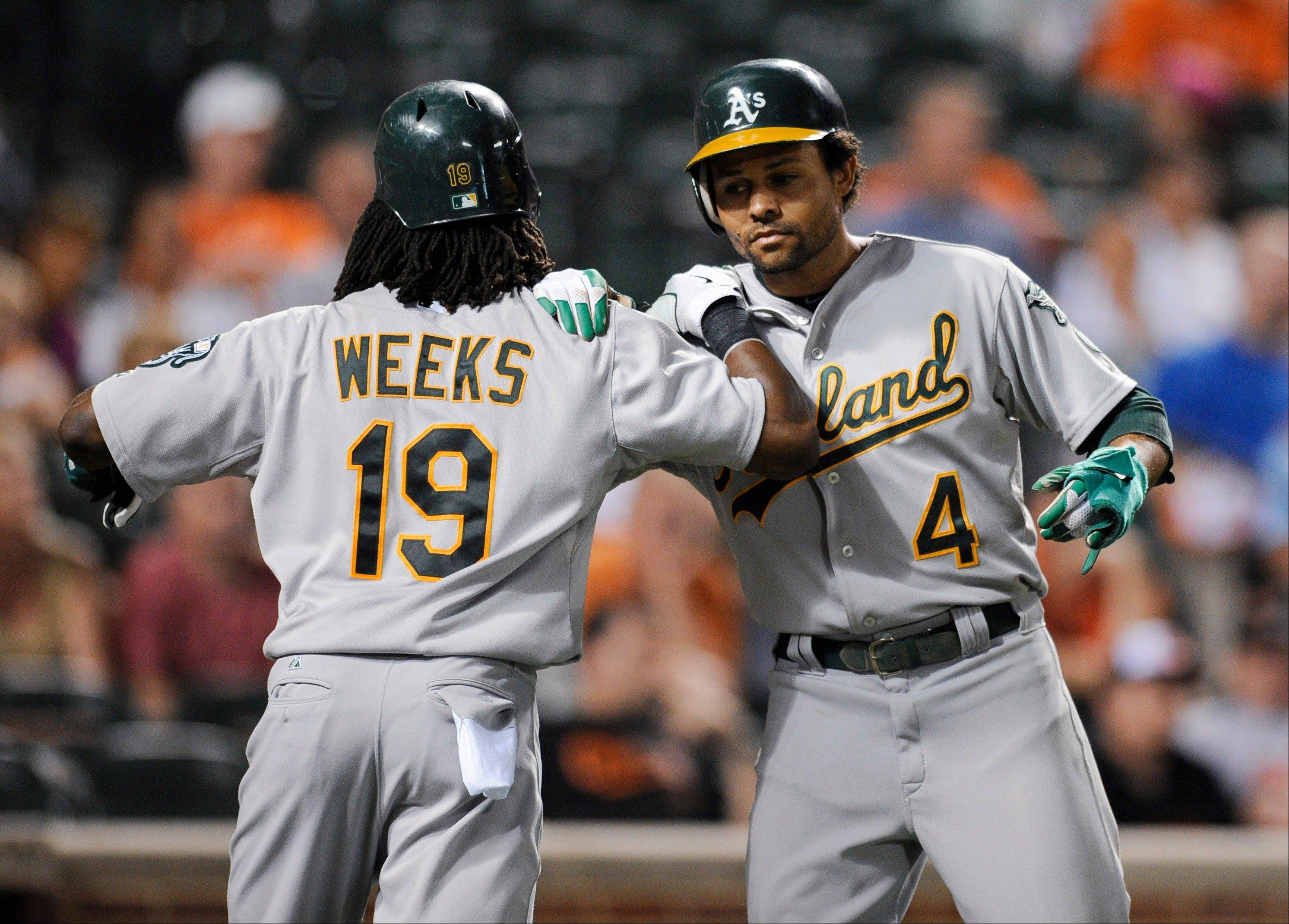 Oakland's Coco Crisp celebrates with Jemile Weeks after they both scored on a double by Seth Smith during the ninth inning Friday in Baltimore.