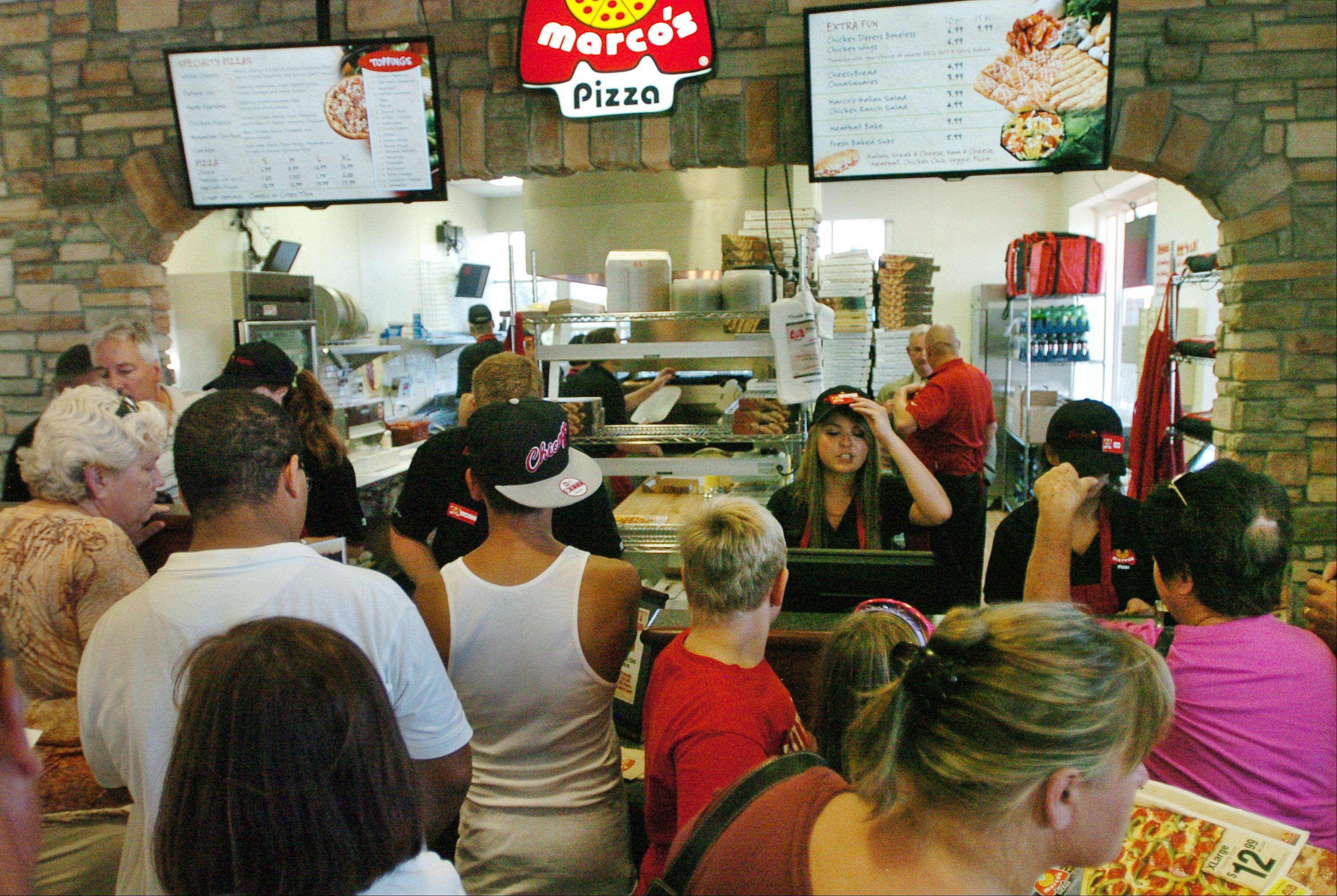 People line up for a chance at free pizza for a year at the new Marco's Pizza in Wheeling.