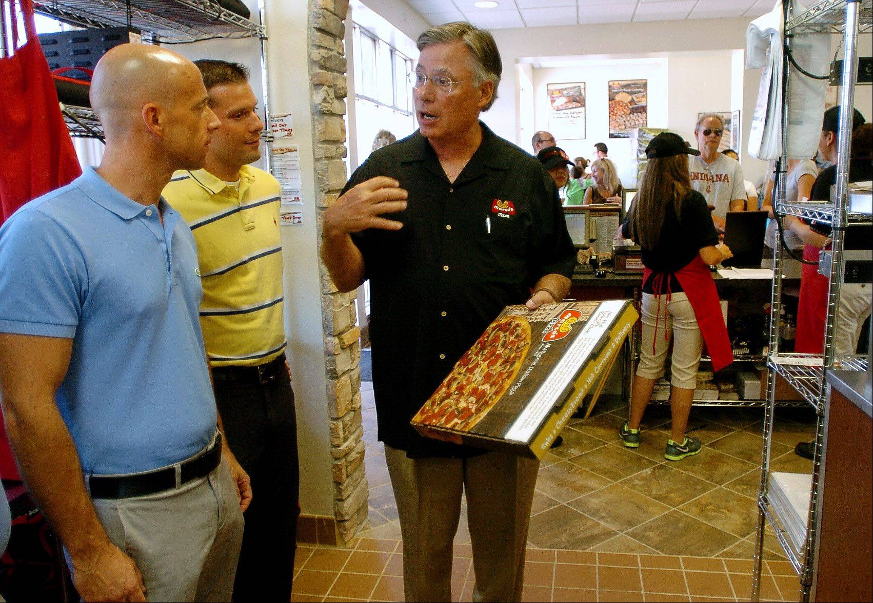 Marco's CEO Jack Butorac, right, talks with Family Video execs Jim Stoner, left, and Rob Voltz at the opening of a new Marco's Pizza in Wheeling.