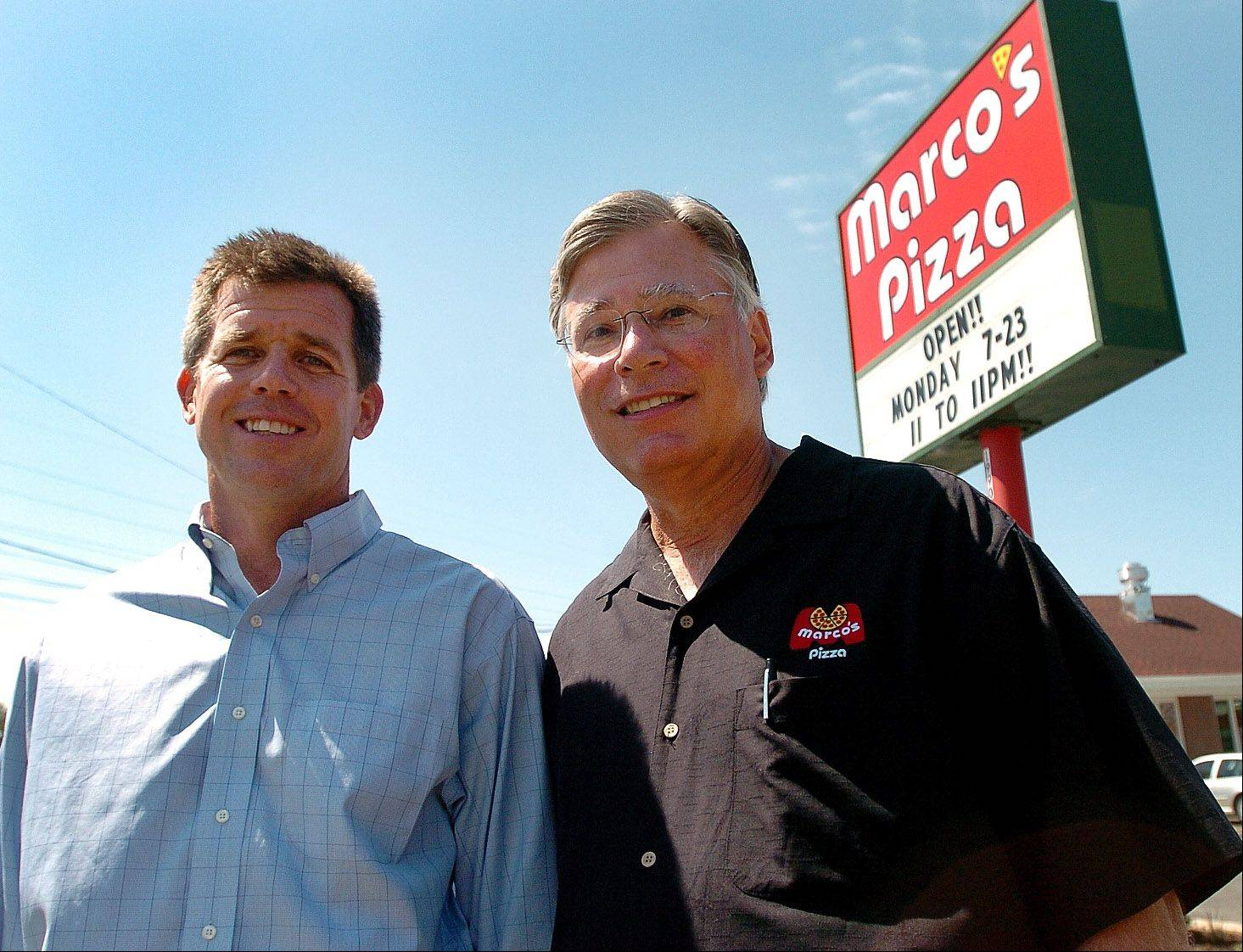 Family Video CEO Keith Hoogland, left, and Marco's Pizza CEO Jack Butorac stand in front of the new Marco's Pizza in Wheeling.