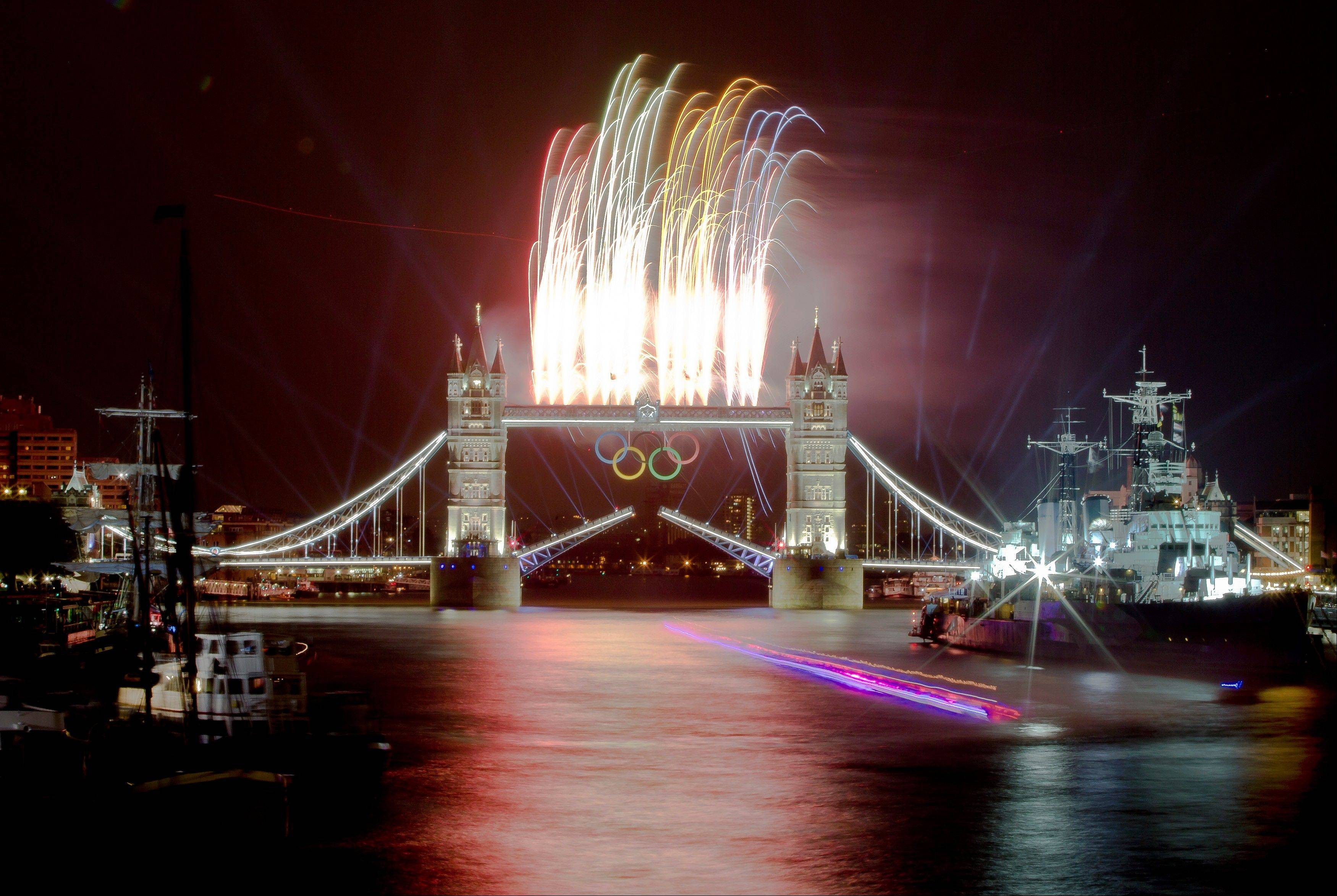 A speedboat carrying the Olympic Flame leaves a trail on this slow exposure photograph as fireworks explode above the iconic Tower Bridge over the River Thames in central London, decorated with Olympic rings, during the Opening Ceremony at the 2012 Summer Olympics, Friday, July 27, 2012, in London.