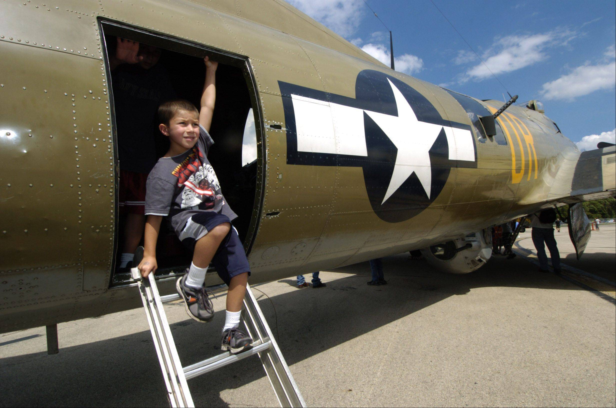 Anthony Michelotti, 6, of Palatine exits a B-17, one of three World War II planes on display Friday for the Wings of Freedom stop at Chicago Executive Airport in Wheeling. The event is open to the public from 9 a.m. to 5 p.m. today and Sunday and 9 a.m. to noon Monday.