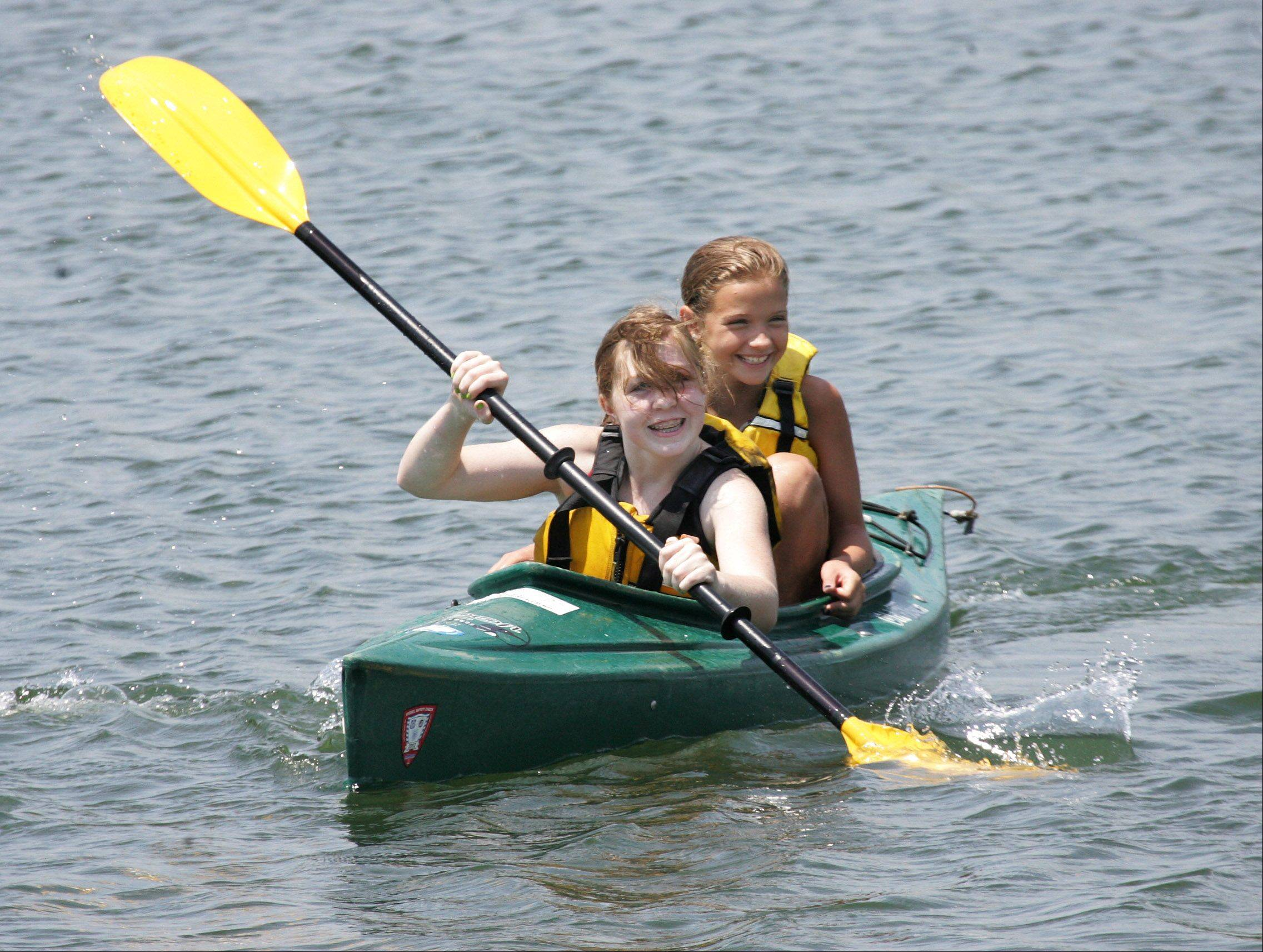 Heather McNaughton, front, and Maddie Nichol, both 12, share a kayak as they race against other members of the Adventures in Nature Camp on a lake at Independence Grove Forest Preserve in Libertyville.