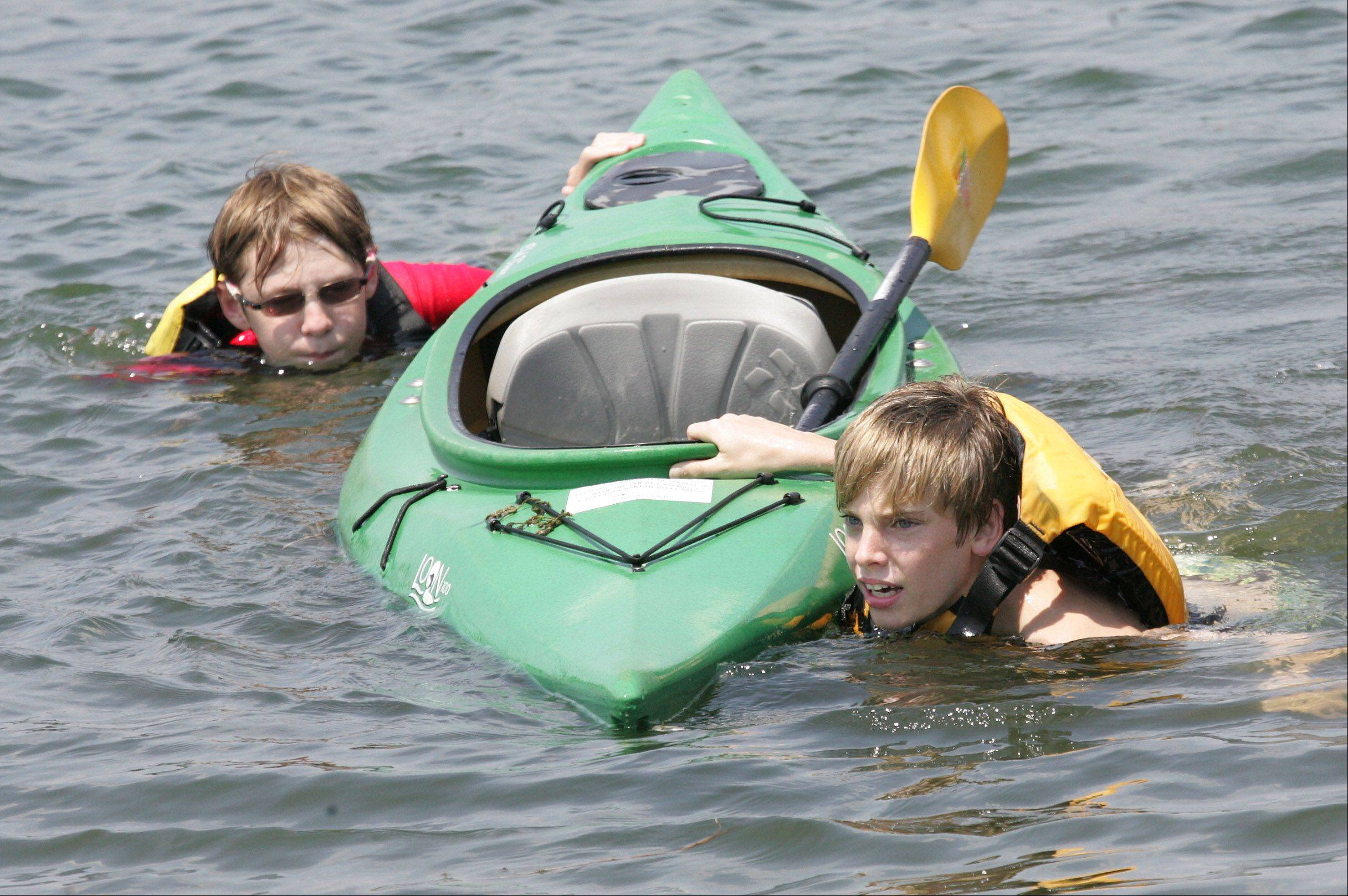 Joseph Harbeck, 13, left, and Tim Paczynski, 14, swim their kayak to shore after it was swamped during an exercise with the Adventures in Nature Camp on a lake at Independence Grove Forest Preserve in Libertyville.
