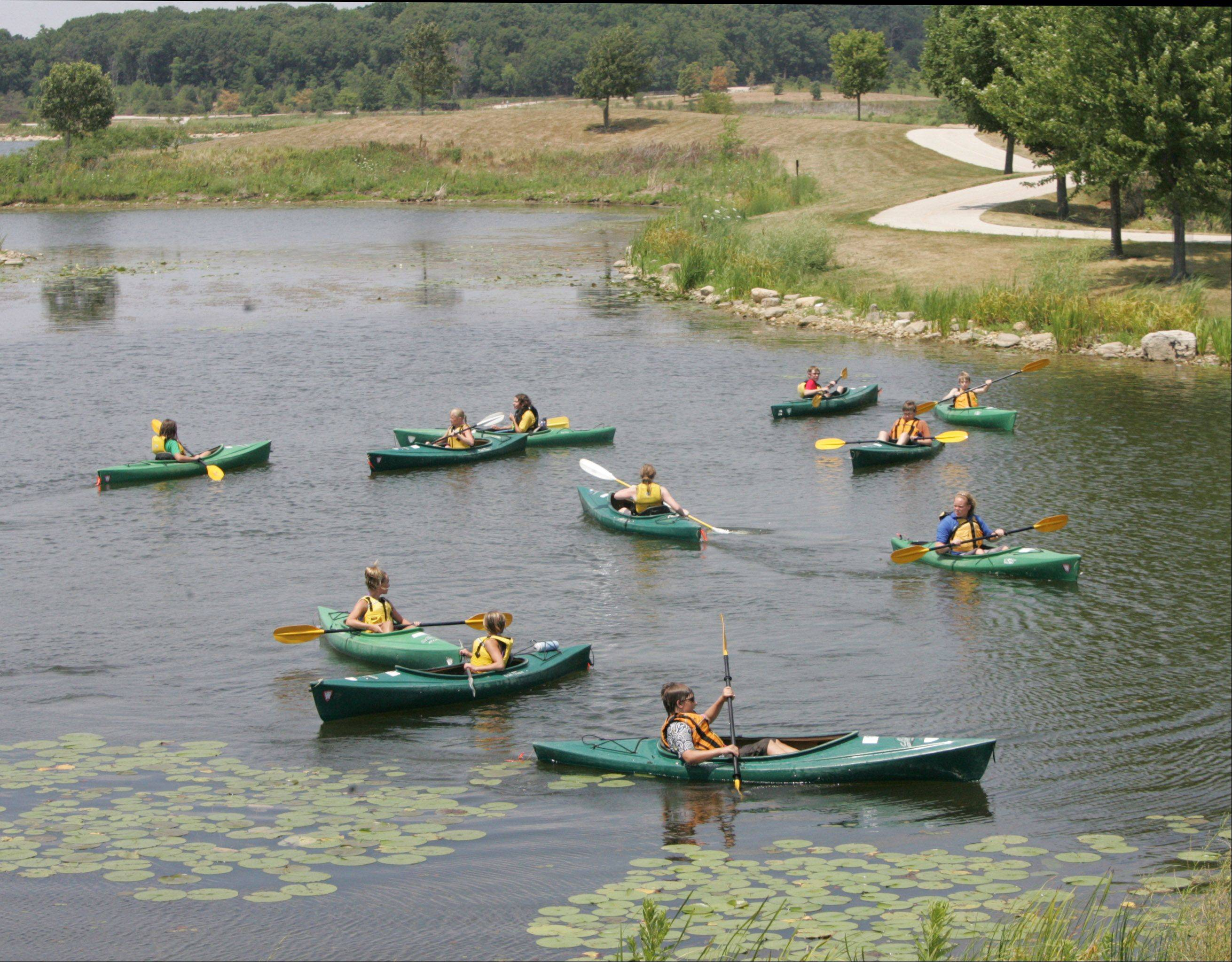 Members of the Adventures in Nature Camp kayak on a lake at Independence Grove Forest Preserve in Libertyville.