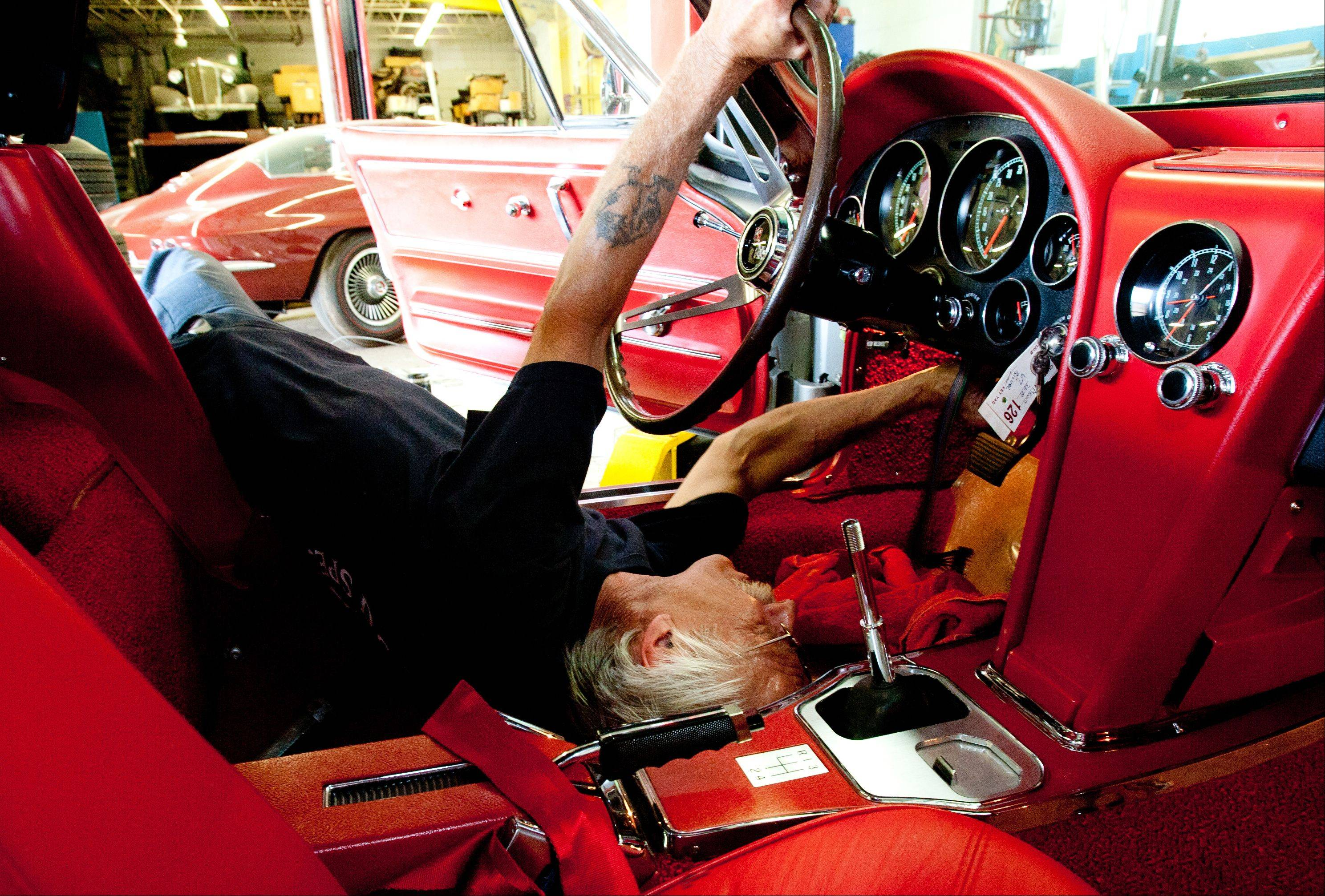 Corvette restoration specialist Cary Kuczkowski of D&M Corvette Specialists in Downers Grove finishes reassembling a dash.