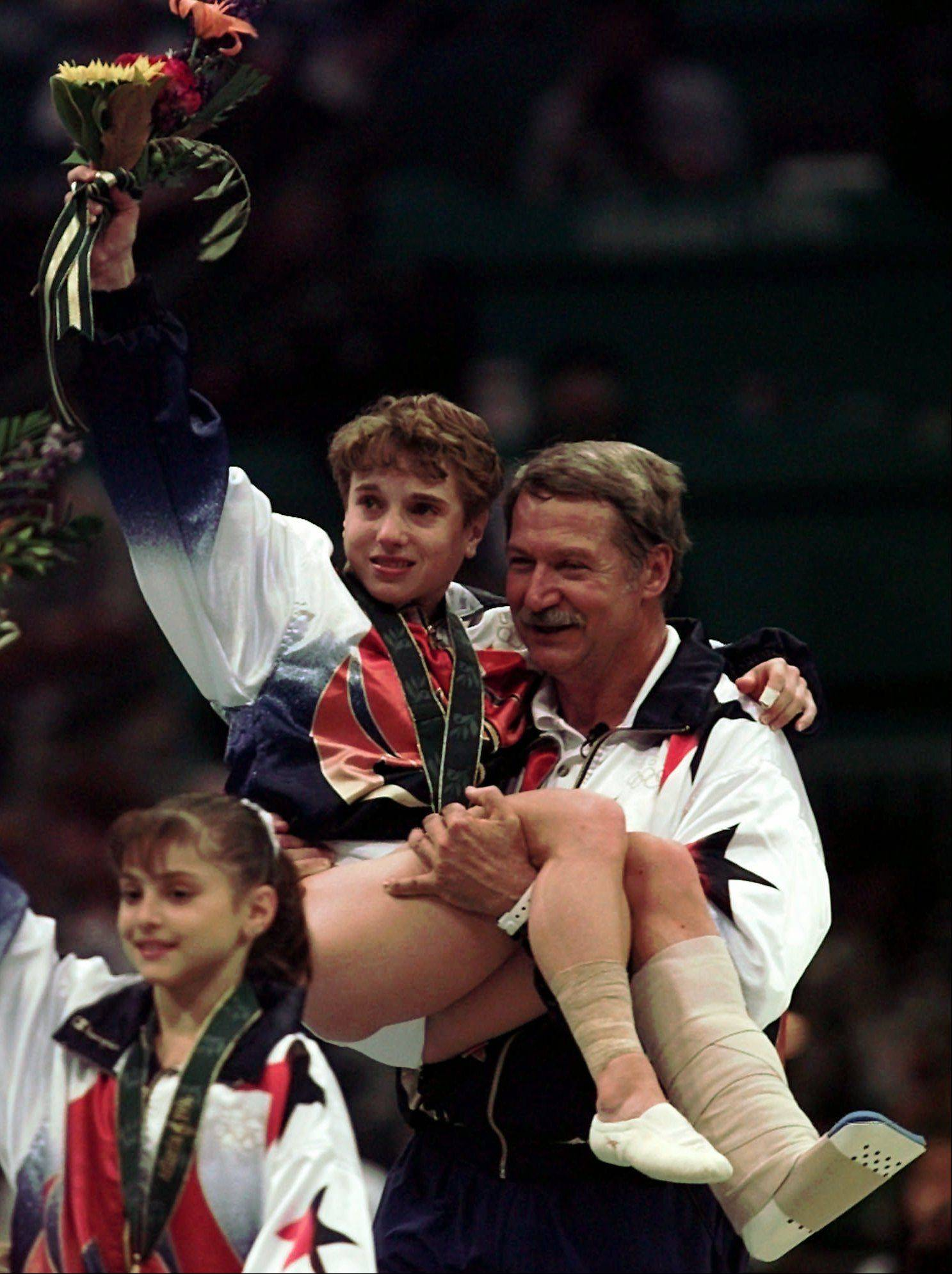 Coach Bela Karolyi carries injured gymnast Kerri Strug after the U.S. women's team received its gold medals in Atlanta in 1996.