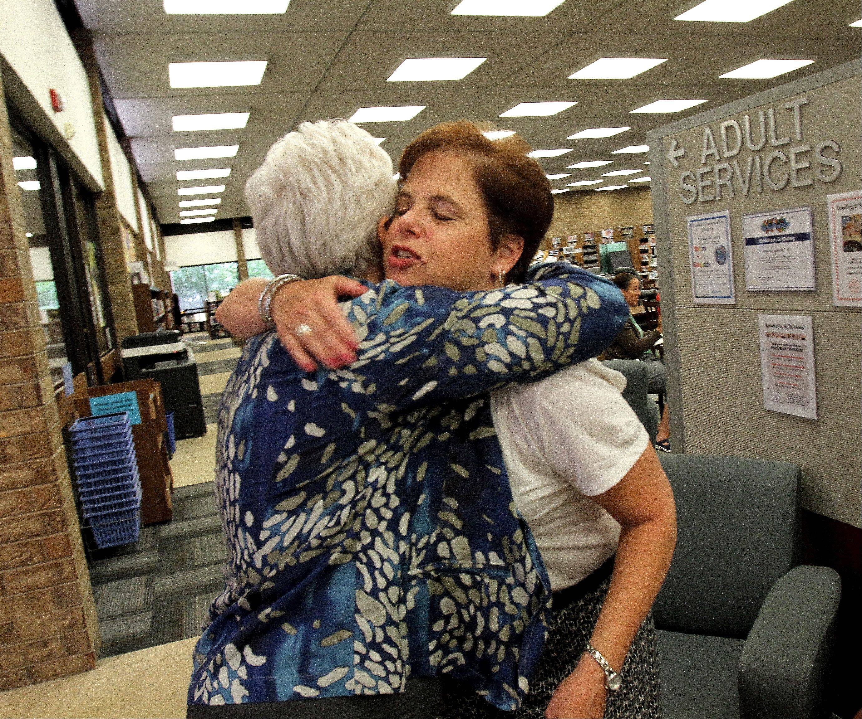 Ann Kennedy, right, hugs Mary Clemens, the interim director of the Carol Stream Public Library, a day after the library board voted to dismiss Kennedy as director.