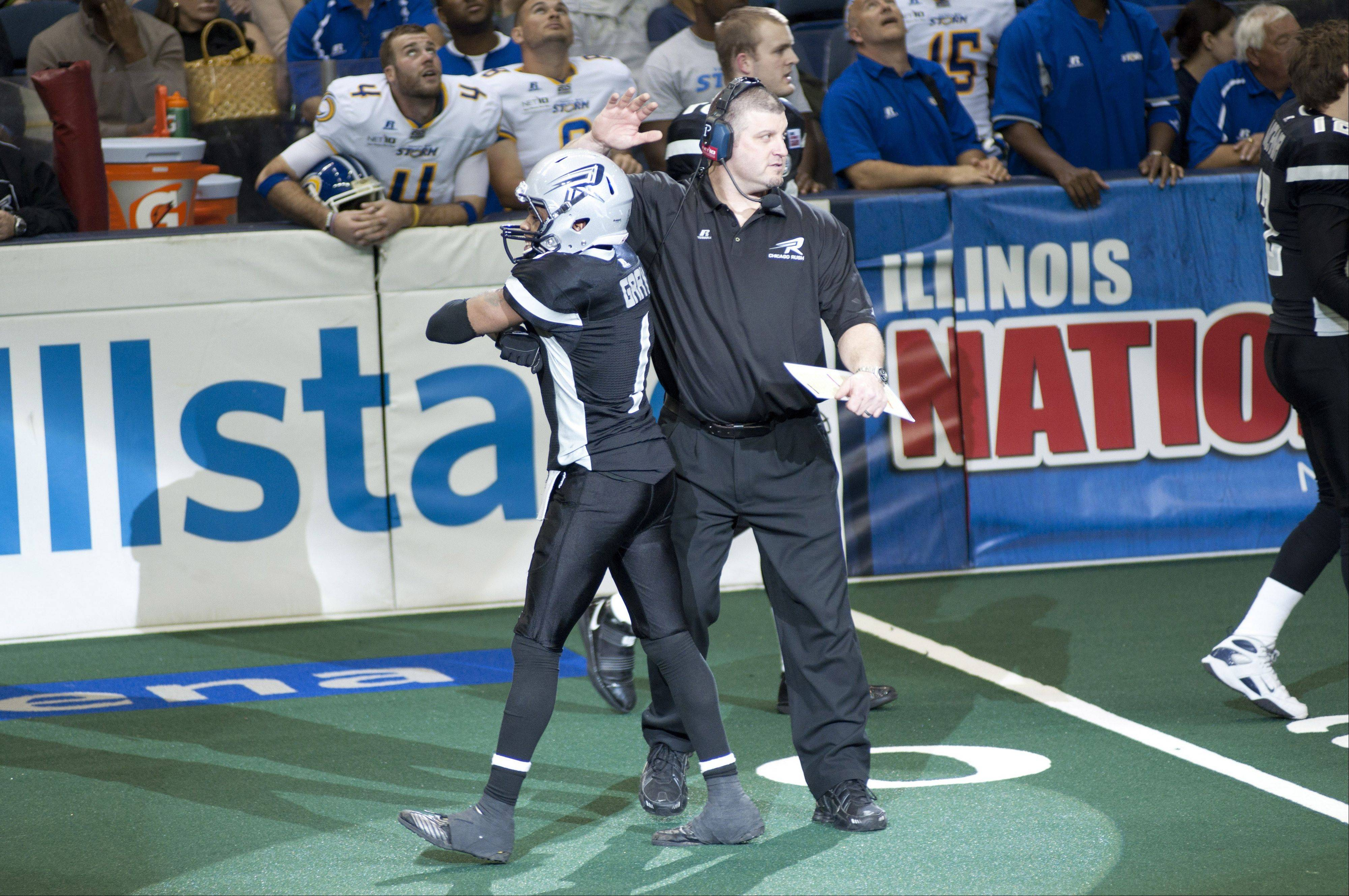 Chicago Rush head coach Bob McMillen, here celebrating a touchdown with wide receiver Reggie Gray while keeping his eyes on the next play, missed the playoffs this season.