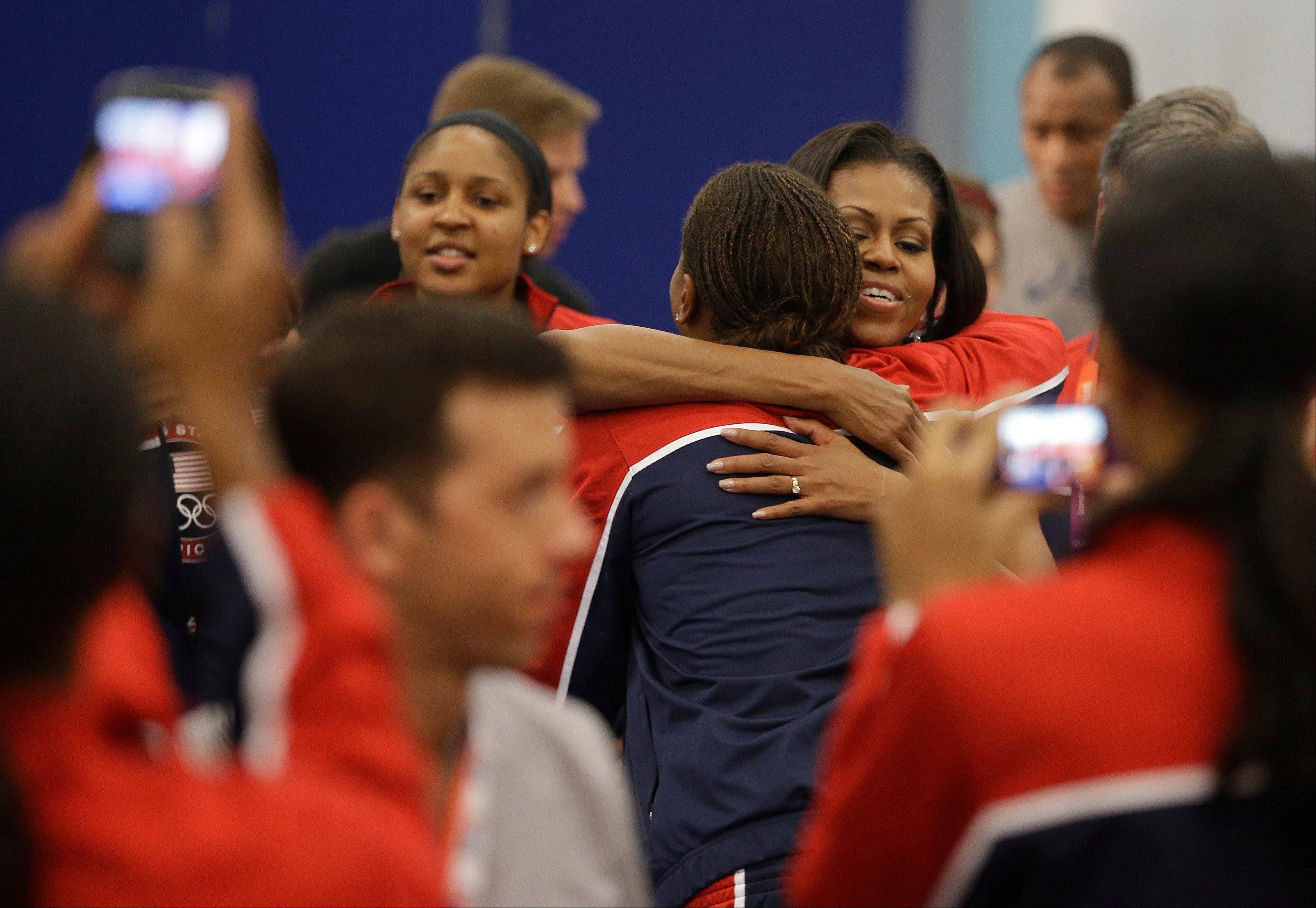 First lady Michelle Obama hugs basketball player Tamika Catchings after speaking during a breakfast Friday with Team USA at the 2012 Summer Olympics in London.